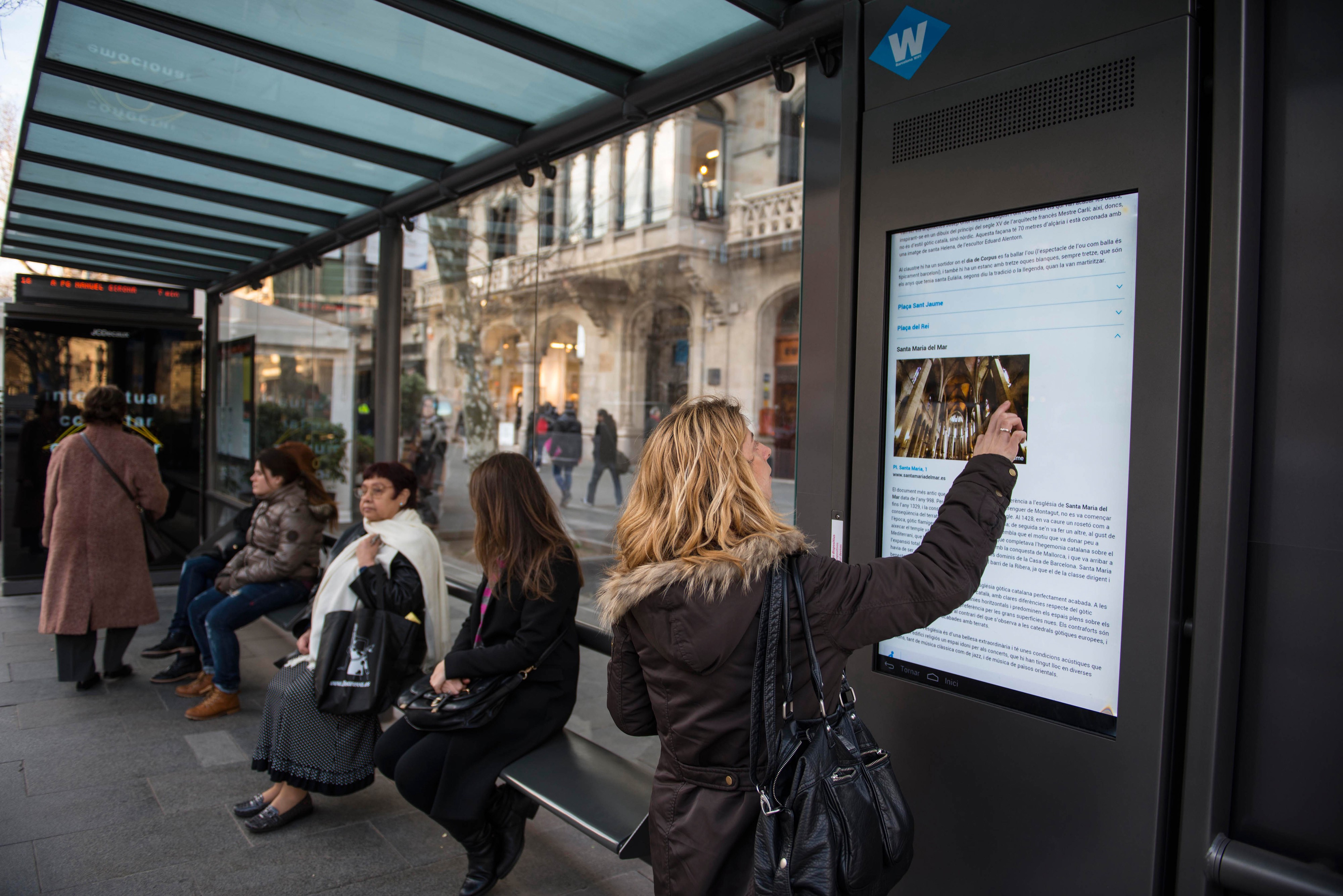A woman in a bus shelter in Barcelona, Spain, reads a video screen for information.