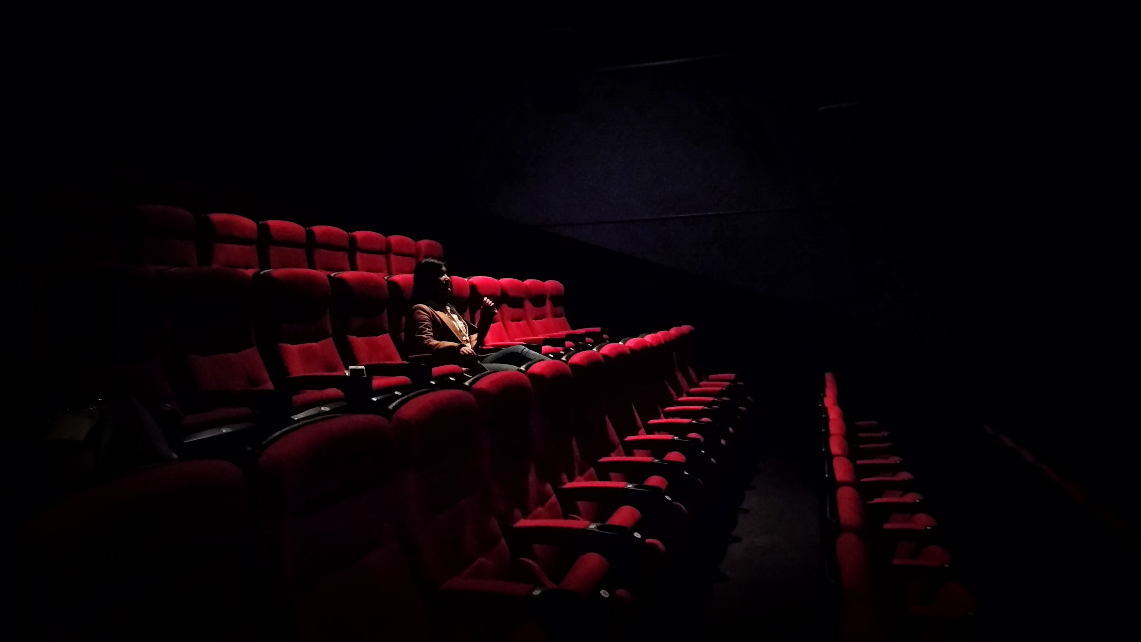 Woman alone in the audience in a movie theater