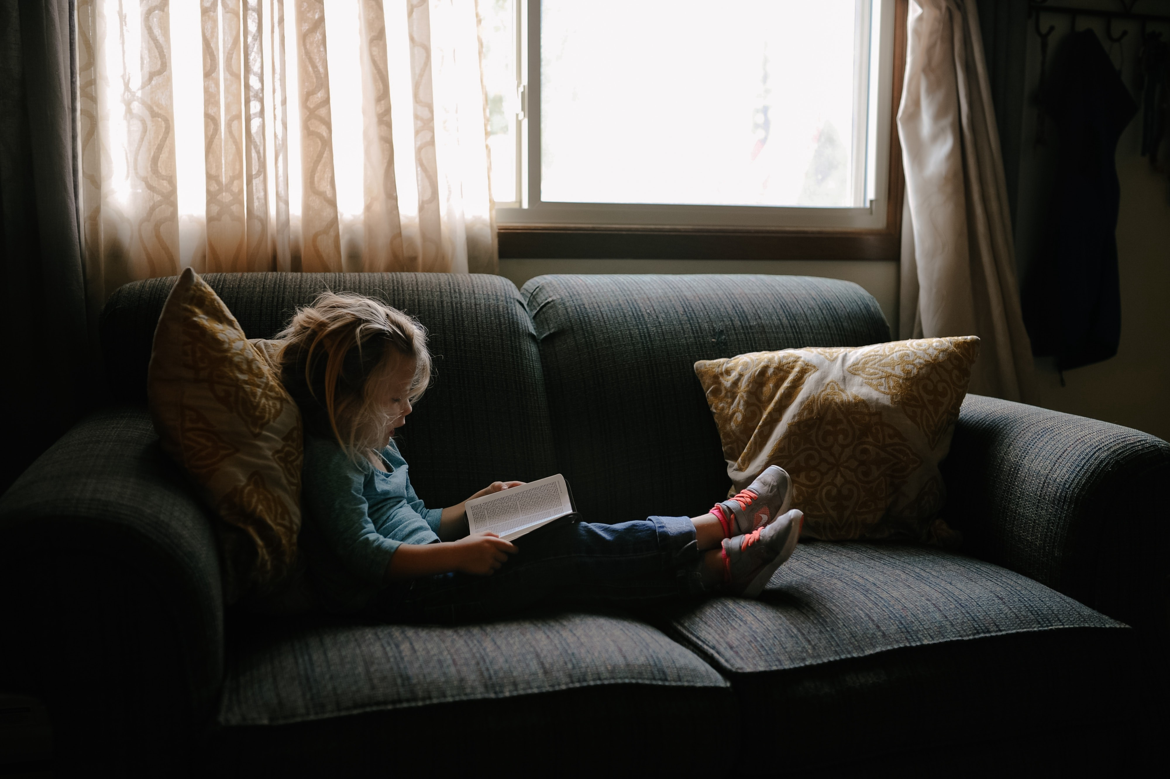 Blond child reclines on a couch with shoes on, looking at a text-heavy book.