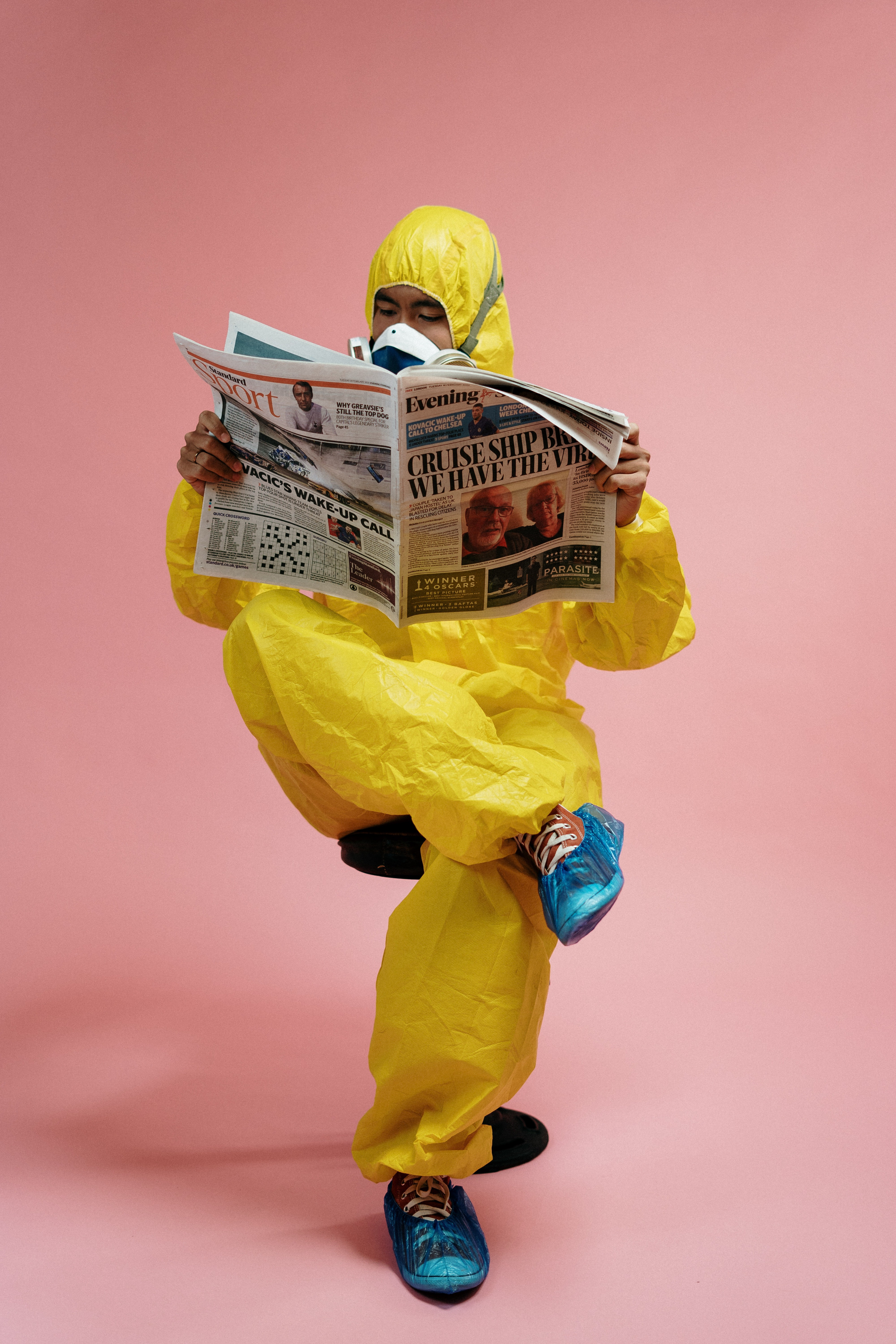 A man in a protective suit reads a newspaper