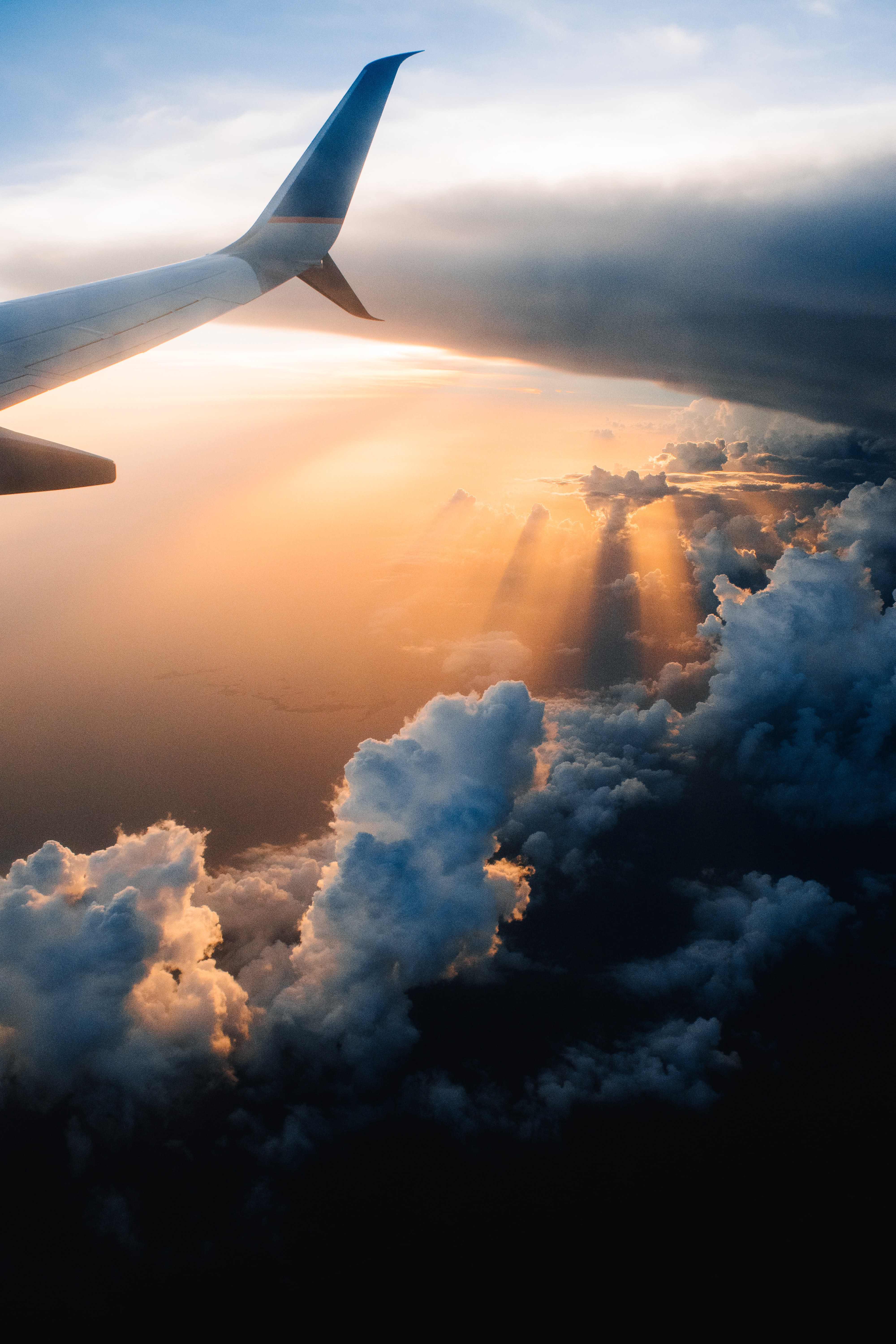 POV from a person in an airplane looking out of the airplane window. A plane wing soars above fluffy clouds in an orange sky.