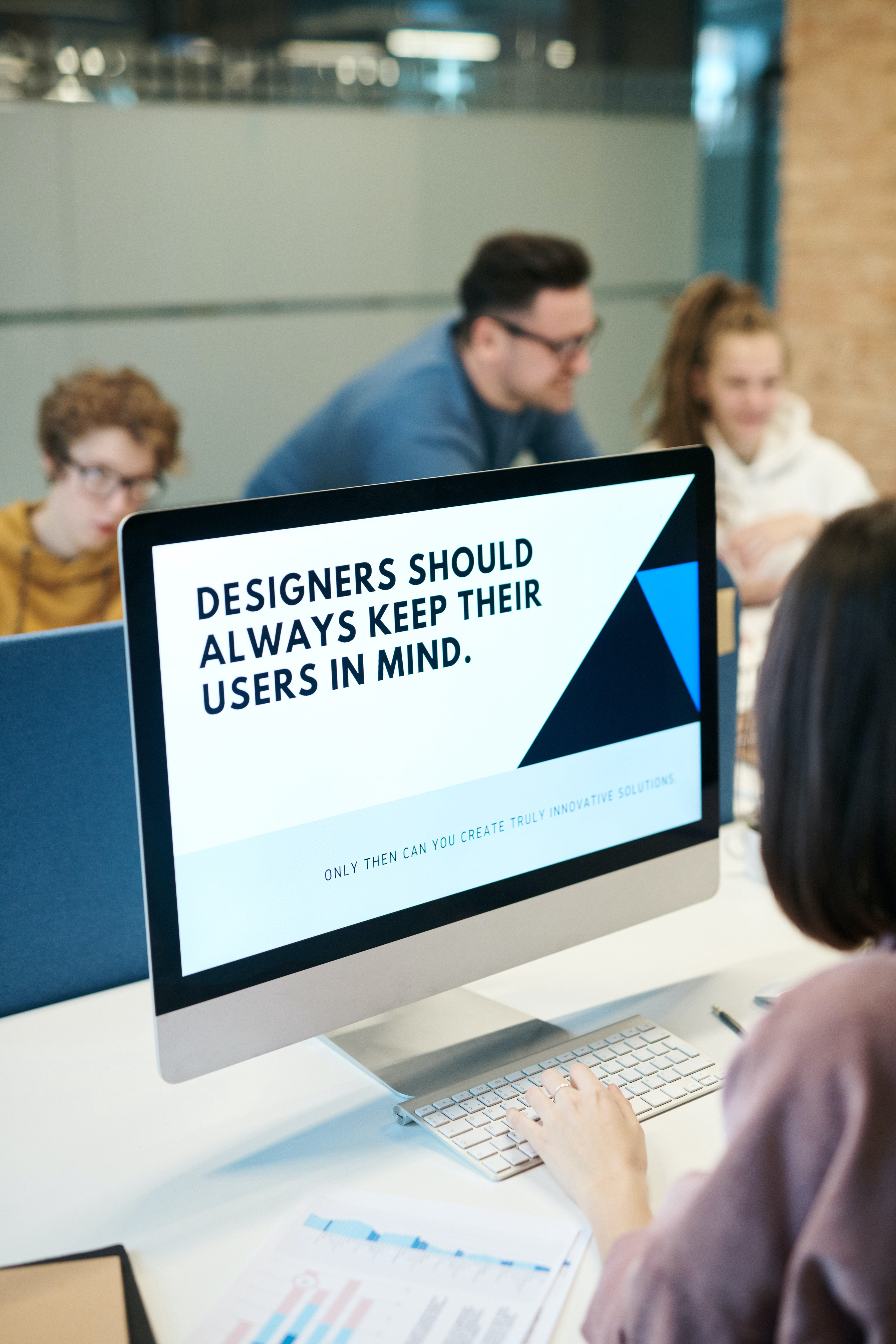 "Woman in a meeting looking at a flat computer monitor that reads, ""Designers should always keep their users in mind""."