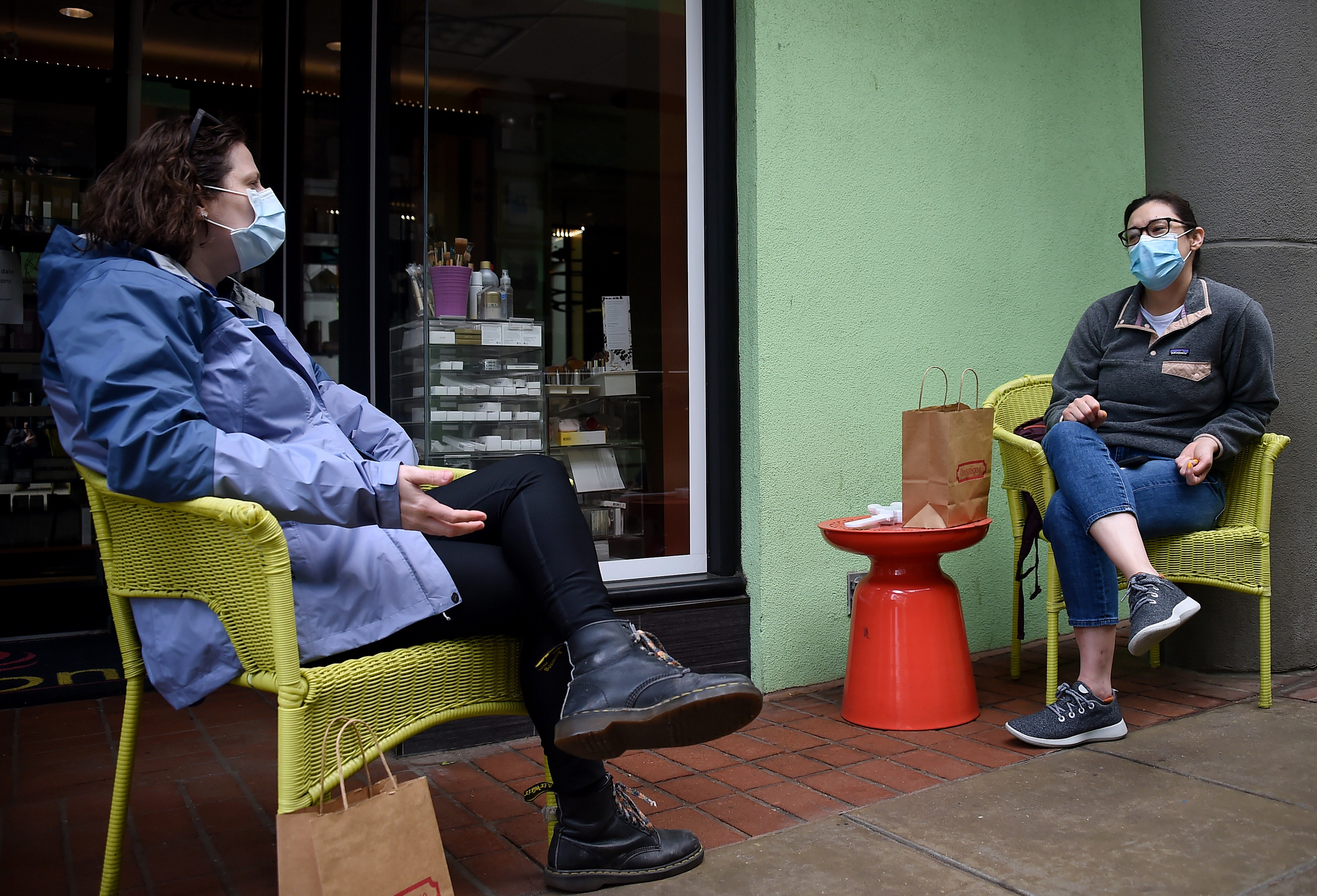 Friends wearing face masks practice social distancing as they chat in front of a shop during the outbreak of COVID-19.