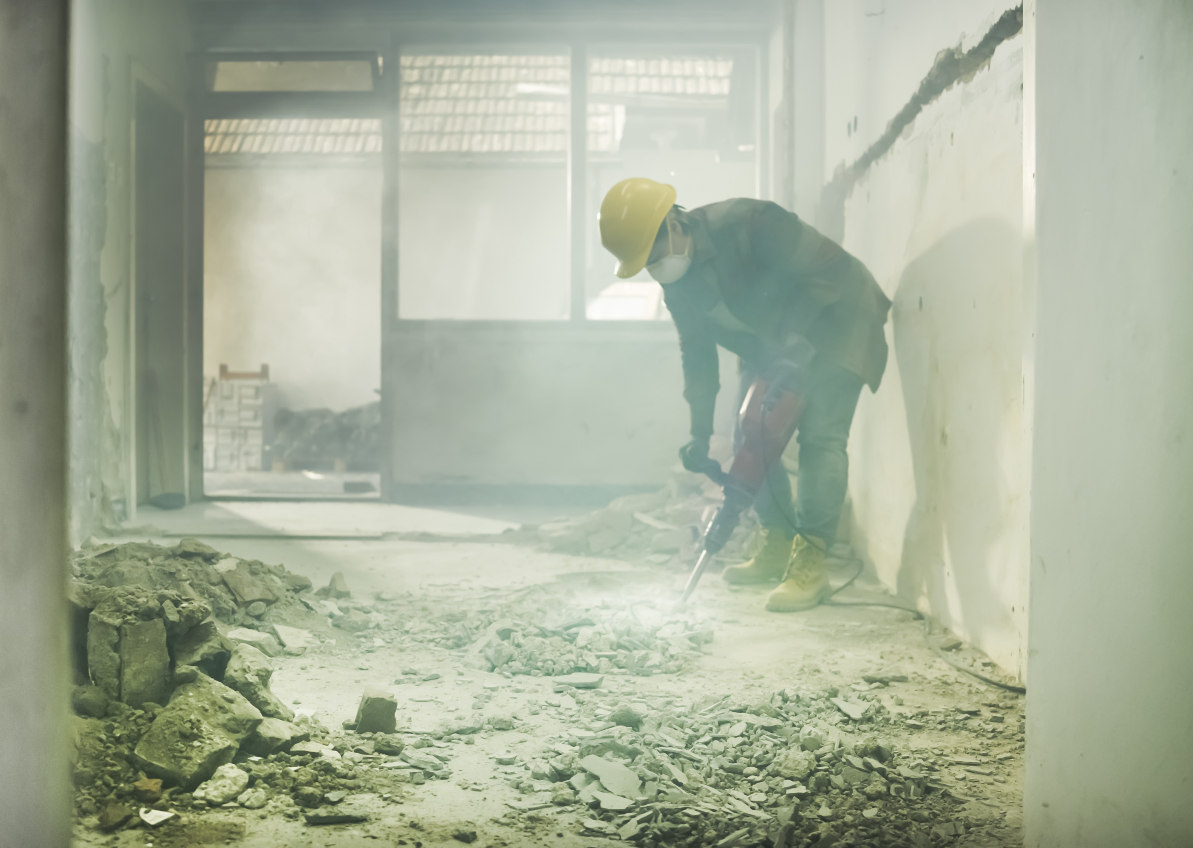 Dust surrounds a construction worker wearing a mask as they drill into a floor.