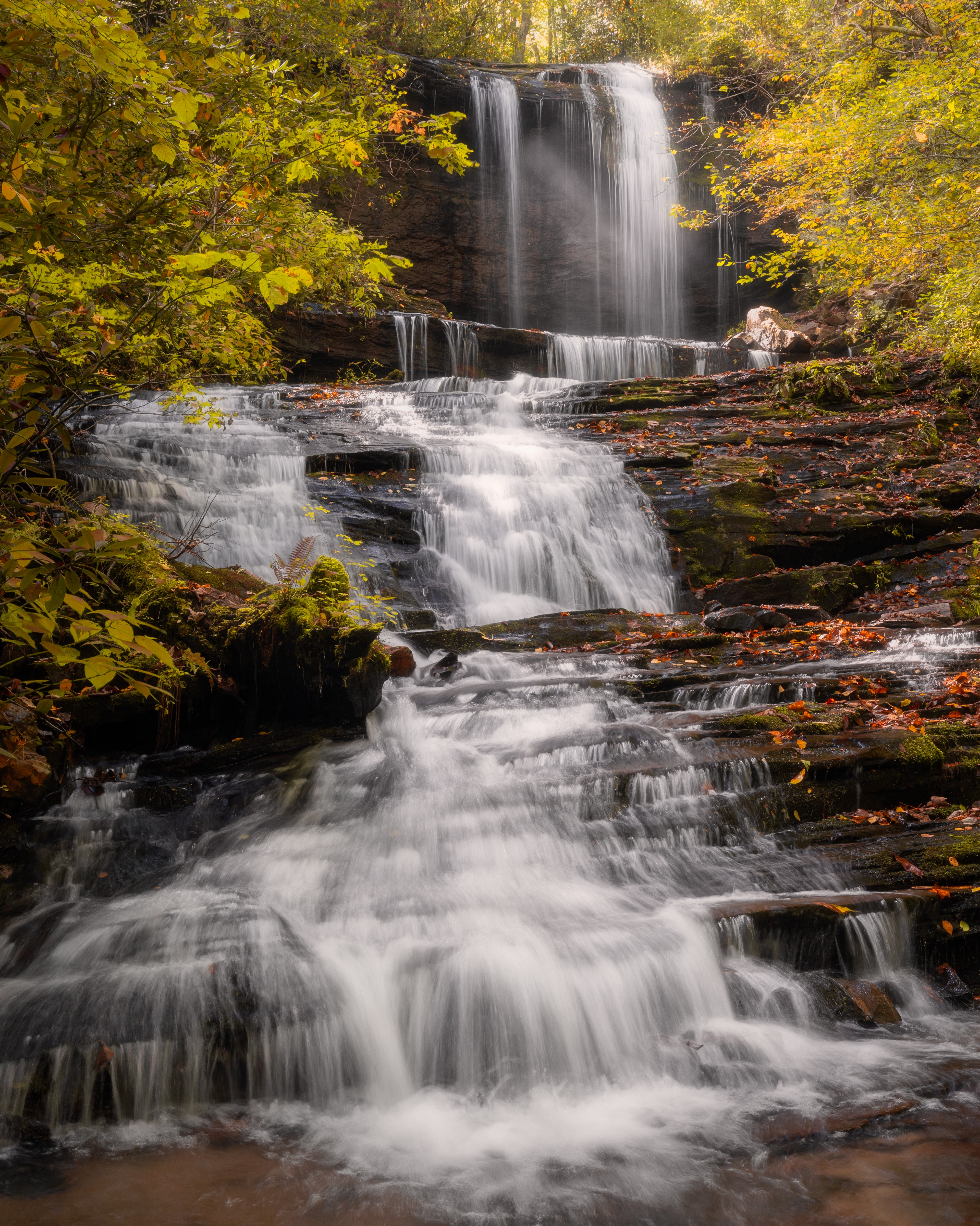 Waterfall cascading over rock shelves with fall foliage lining the side of the stream.