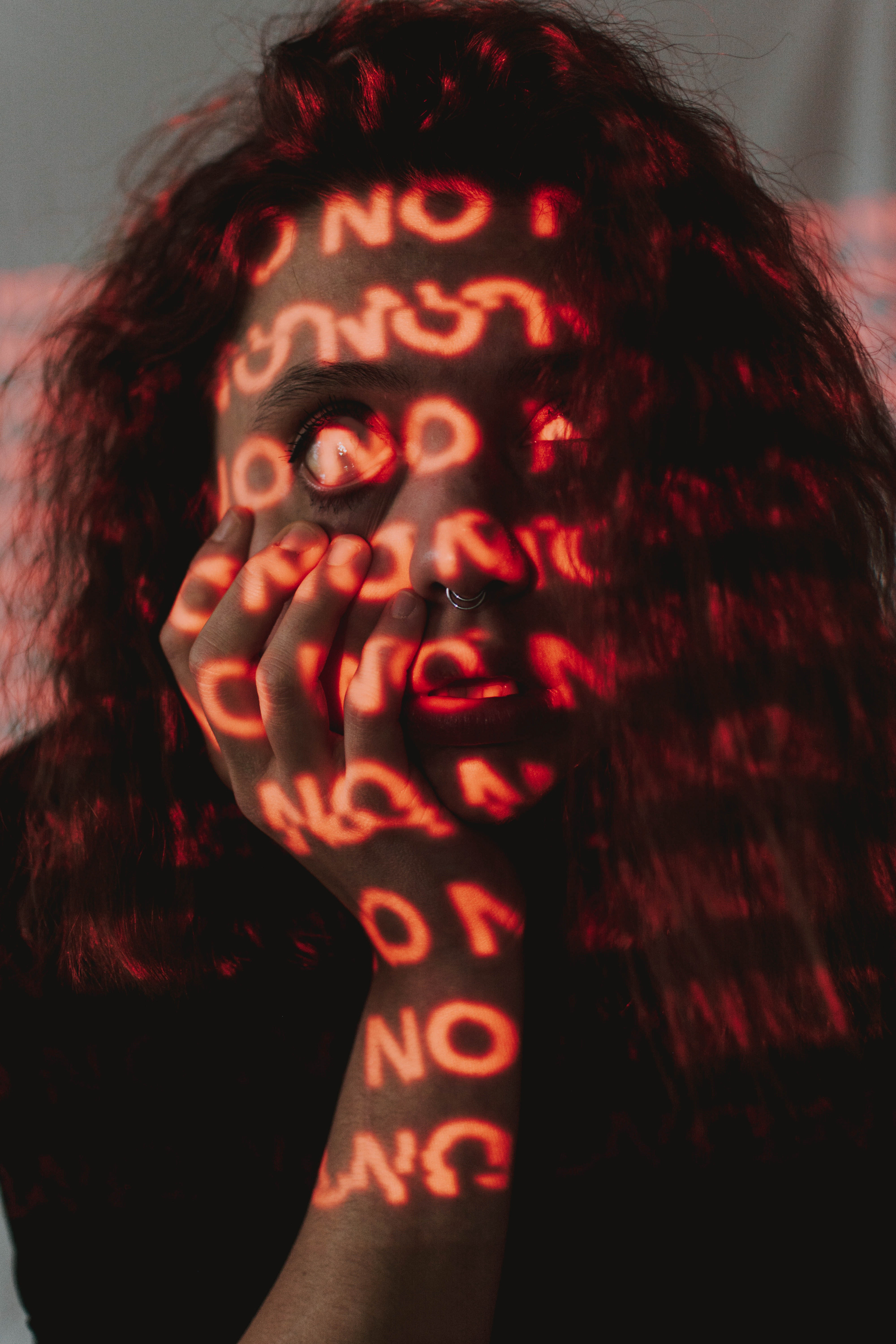 """woman with the word """"no"""" projected all over her face and body"""