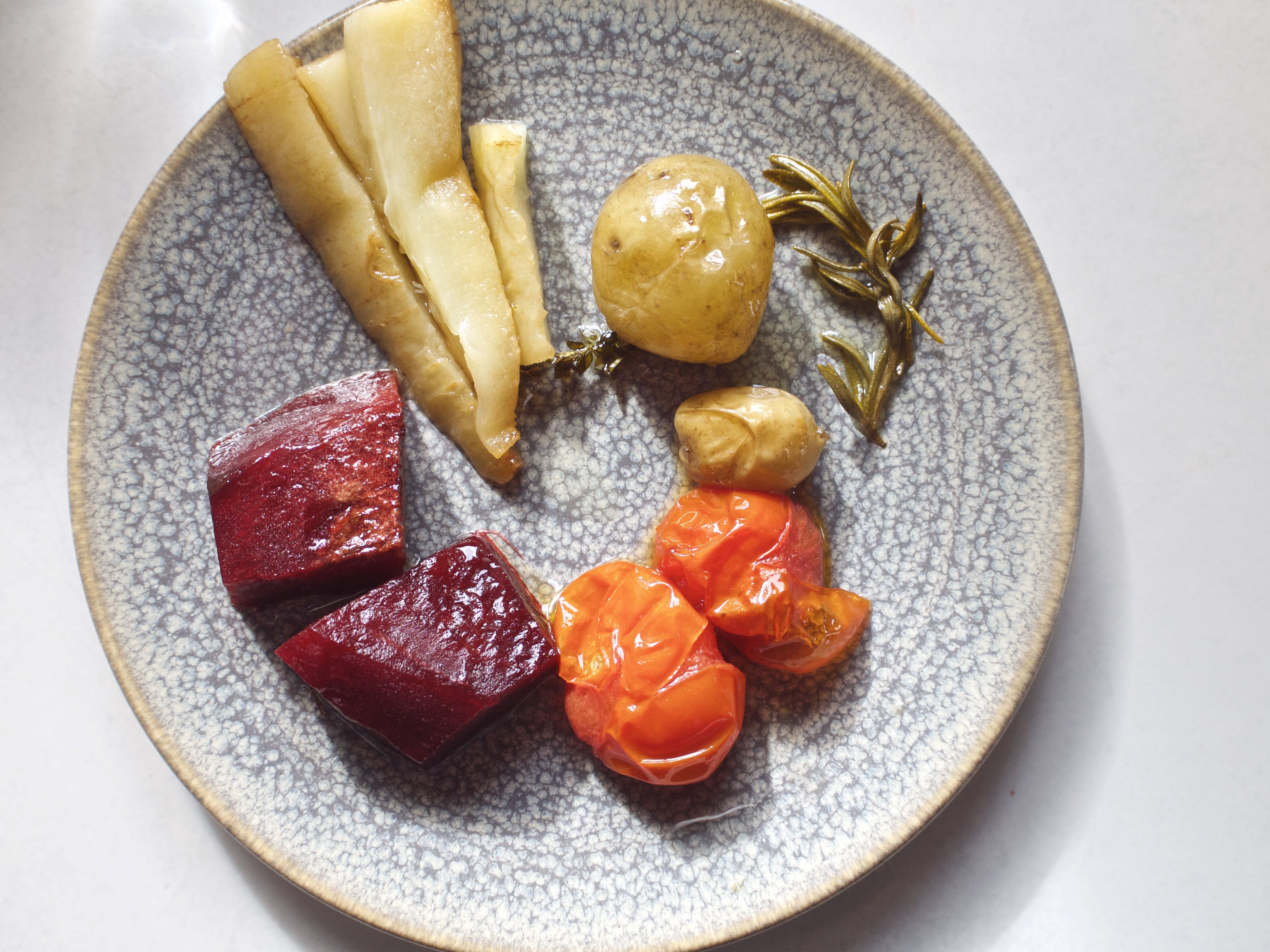 A plated of roasted parsnips, red beets, withered confited tomatoes, potatoes, and thyme.