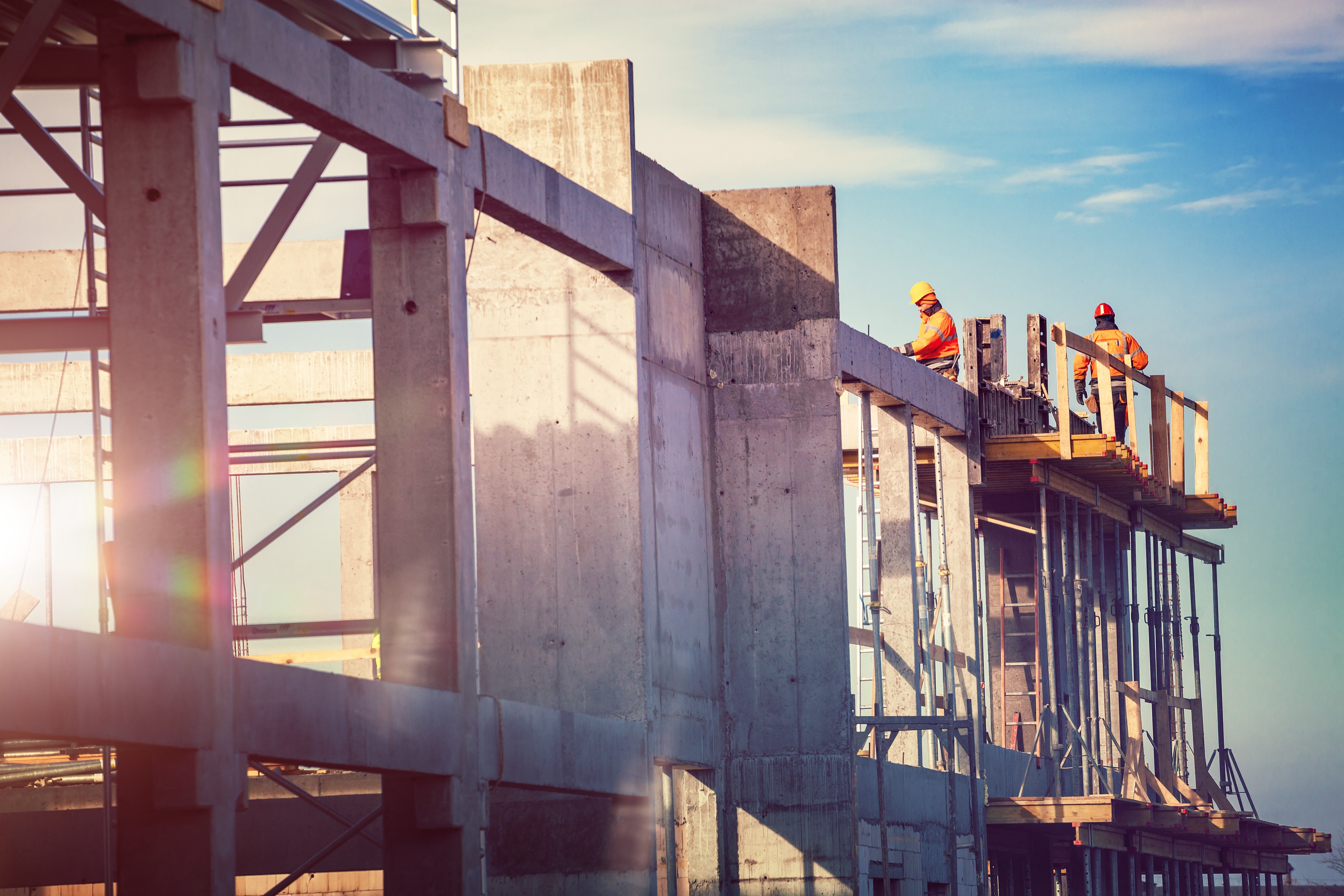 Two construction workers are working on top of a partially constructed concrete structure.