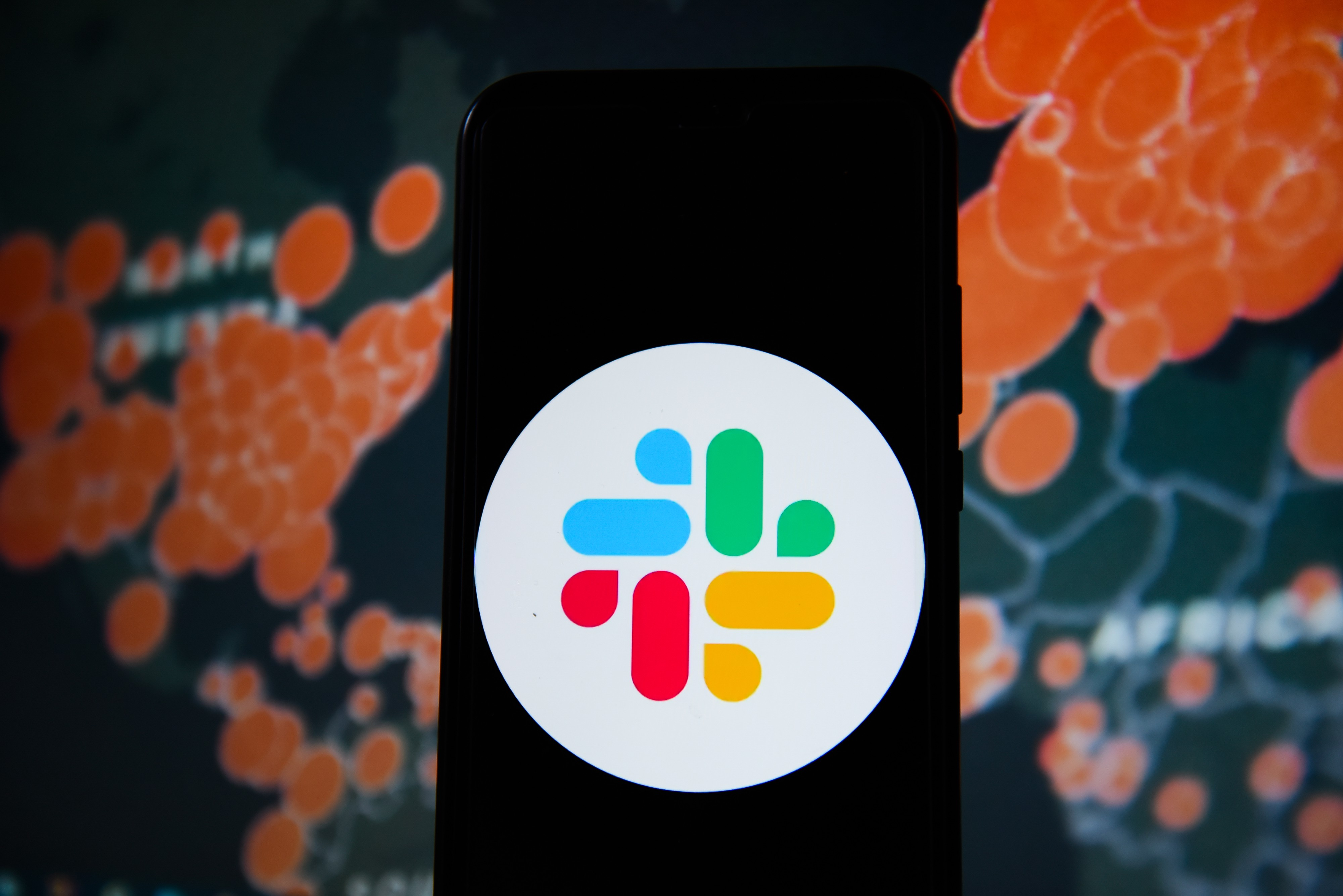 In this photo illustration a Slack logo seen displayed on a phone with a World map of COVID 19 epidemic on the background.