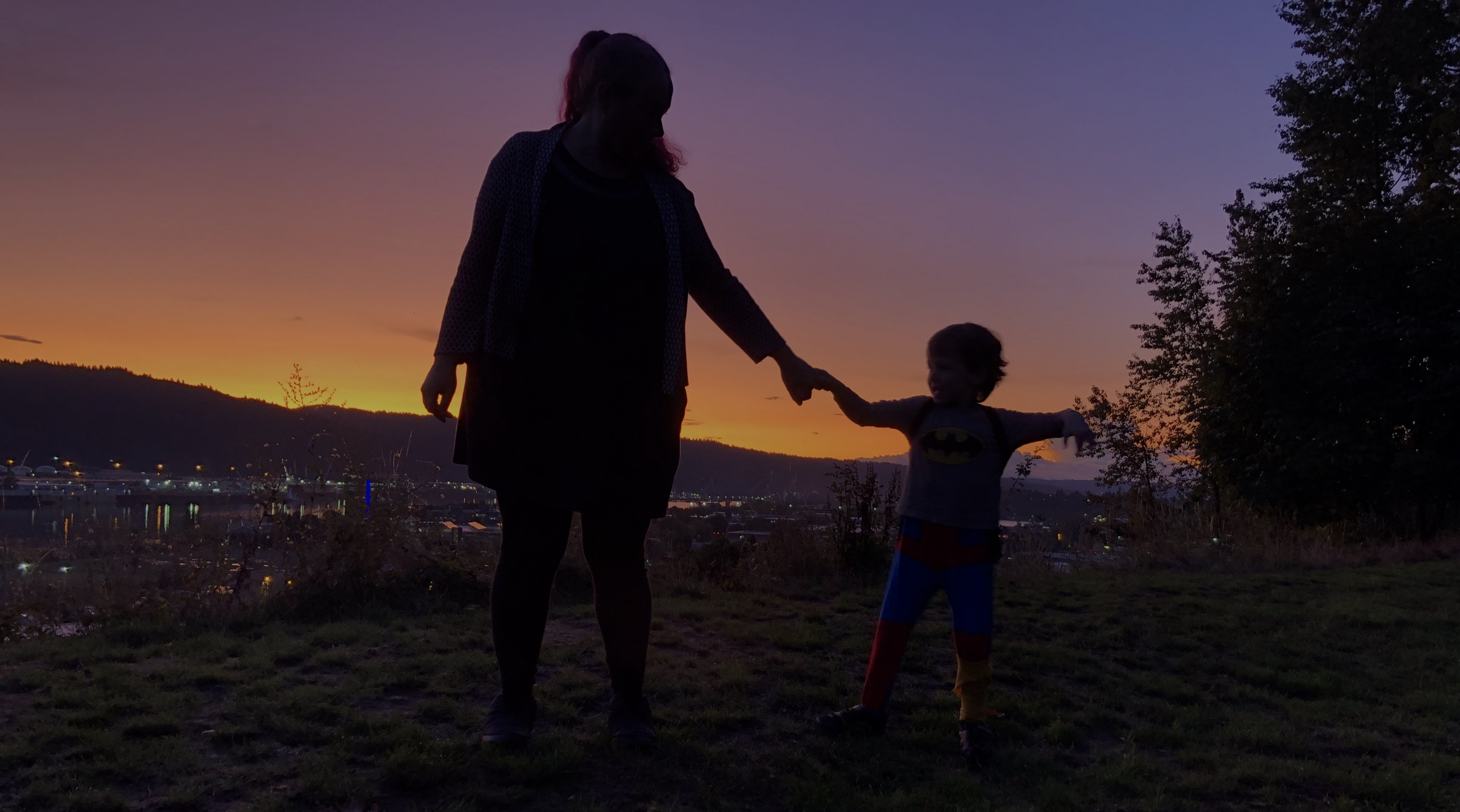Mother and son holding hands and telling tales with the sunset in the background.