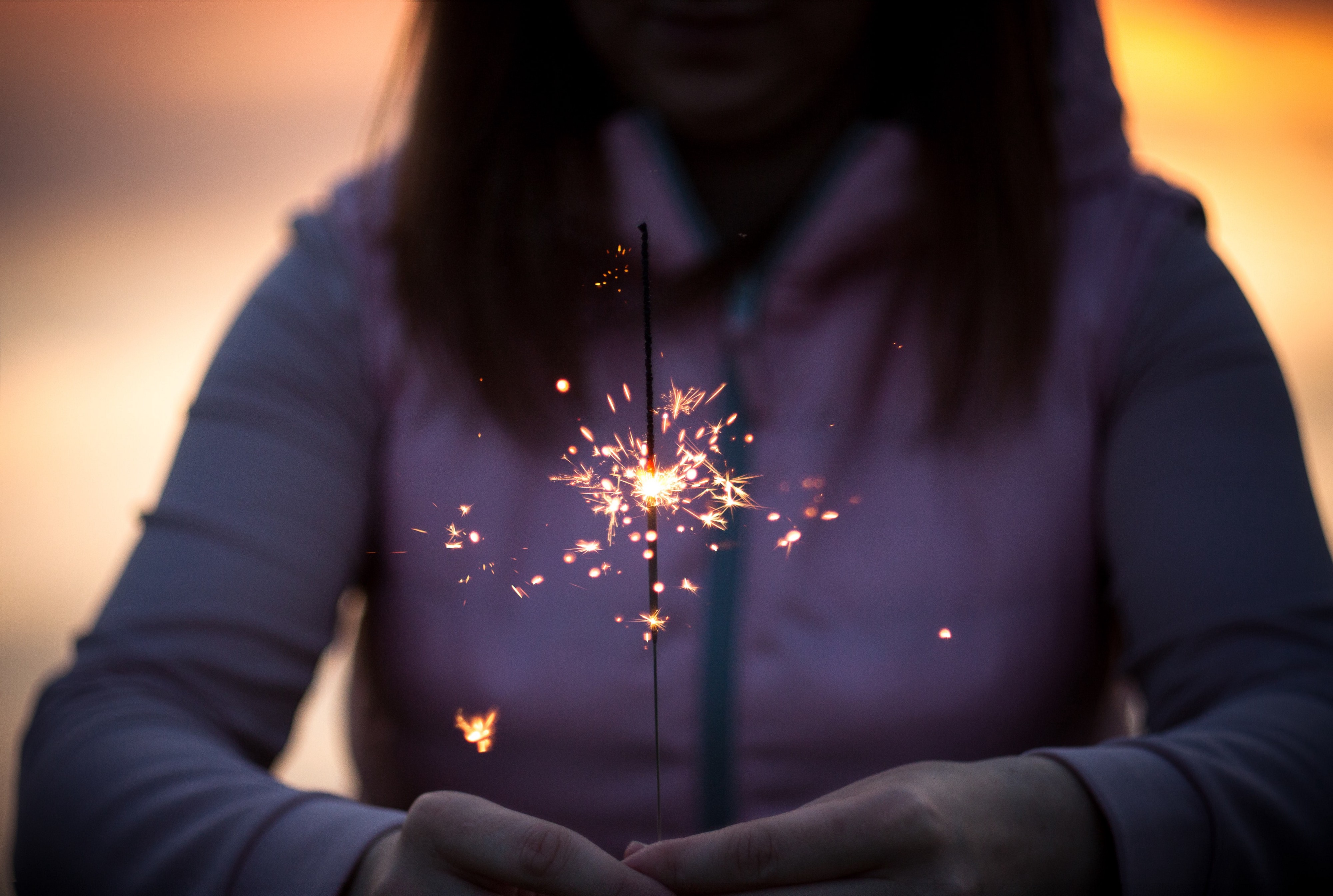 Woman holding sparkler as it burns down