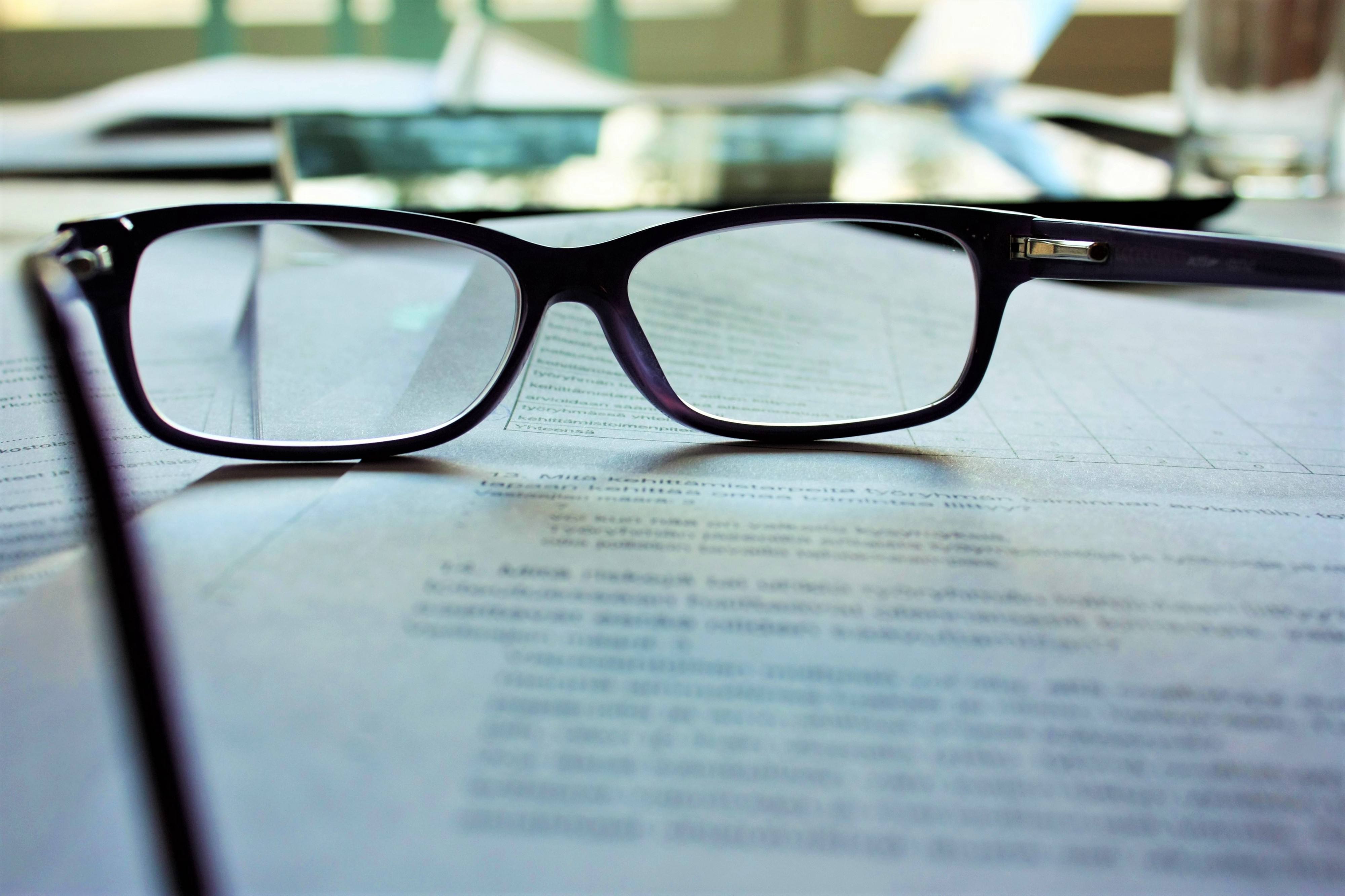 Black oval eye glasses on an out-of-focus stack of paper