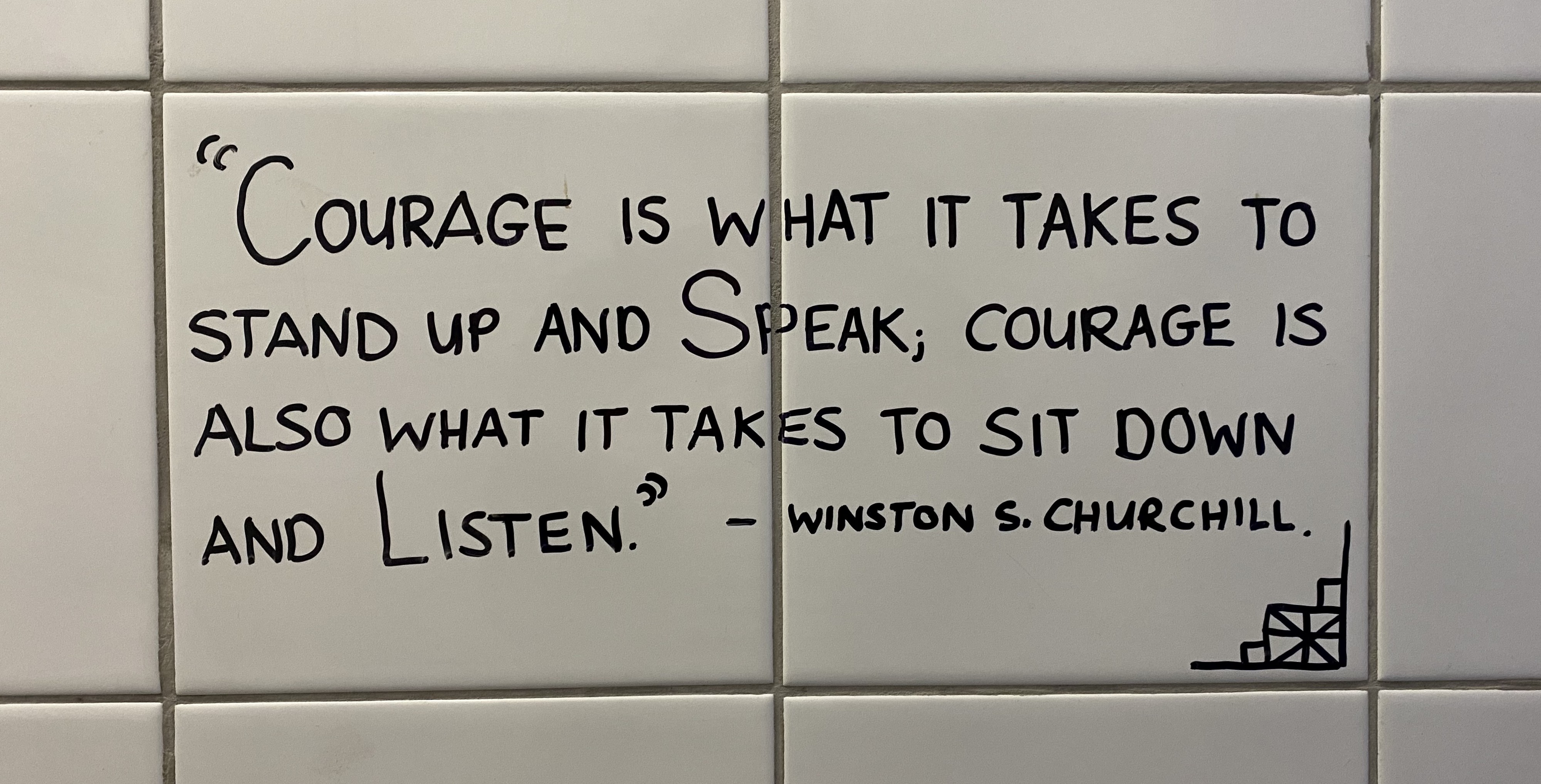 "A Winston Churchill quote on a white tiled wall which reads: ""Courage is what it takes to stand up and speak; Courage is also what it takes to sit down and listen"""