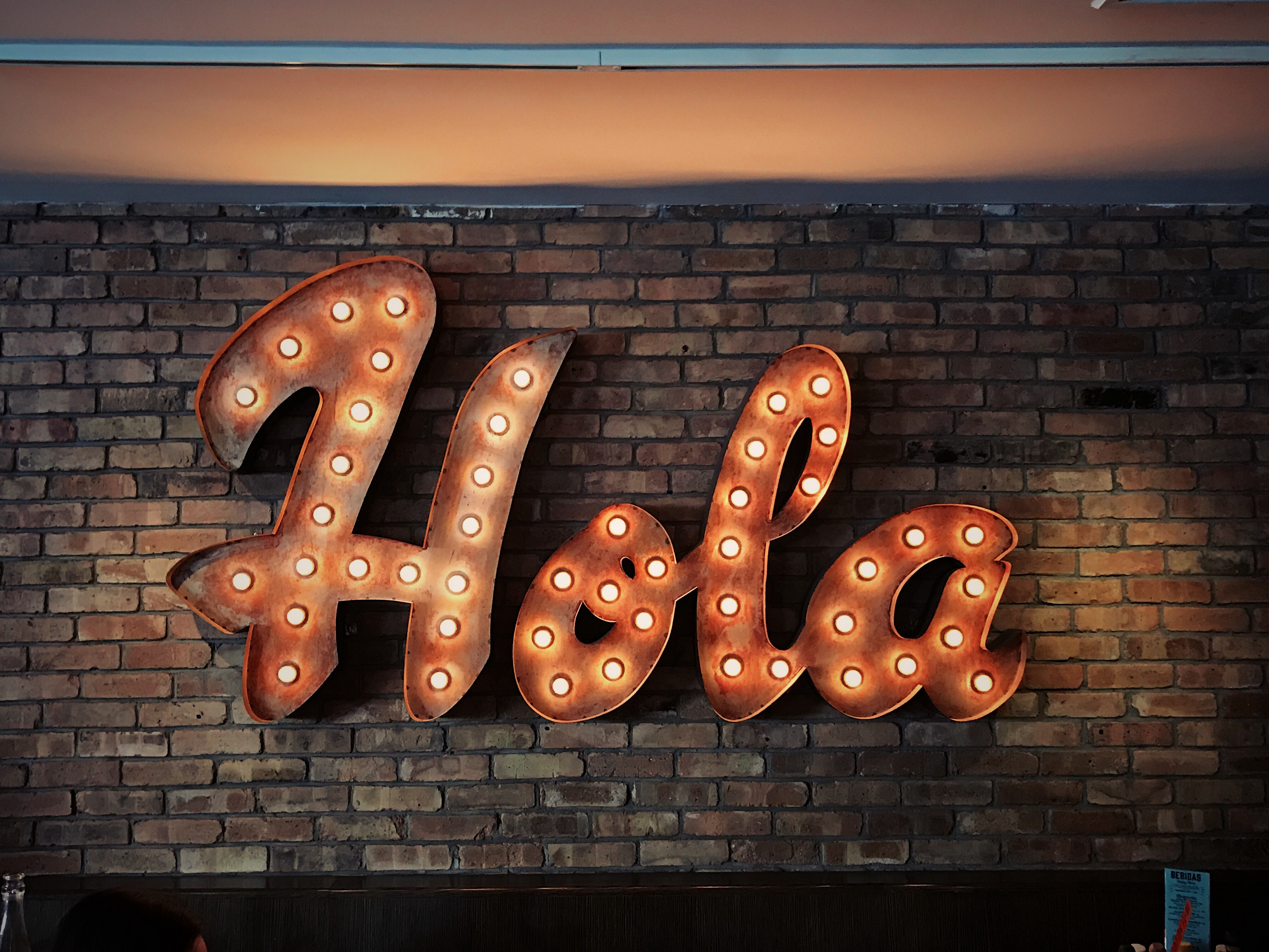 """Curvy font """"Hola"""" sign with orange background and light bulbs on a brick wall"""
