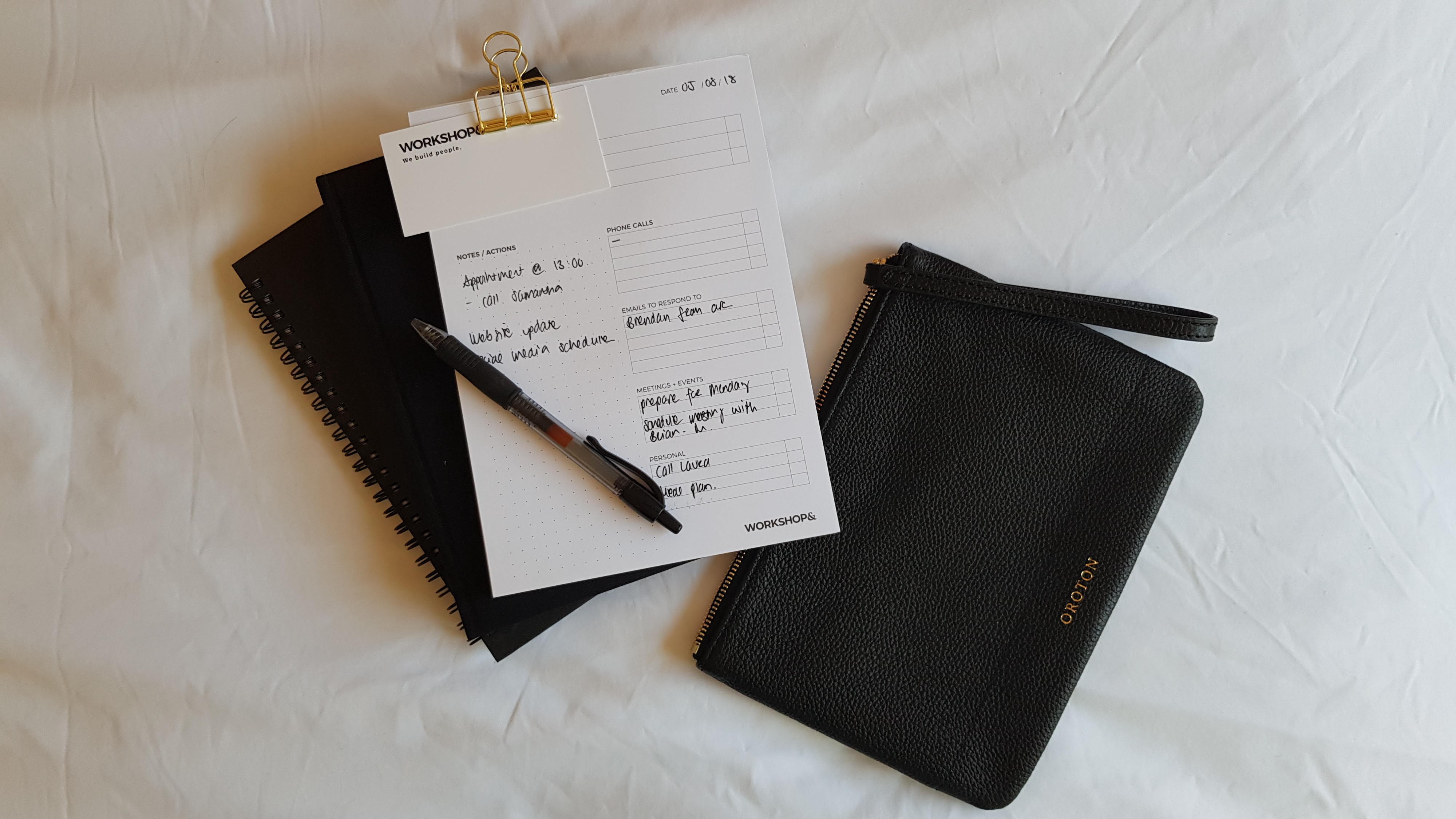A note book with writing on it, on a white bed, with a small black purse next to it