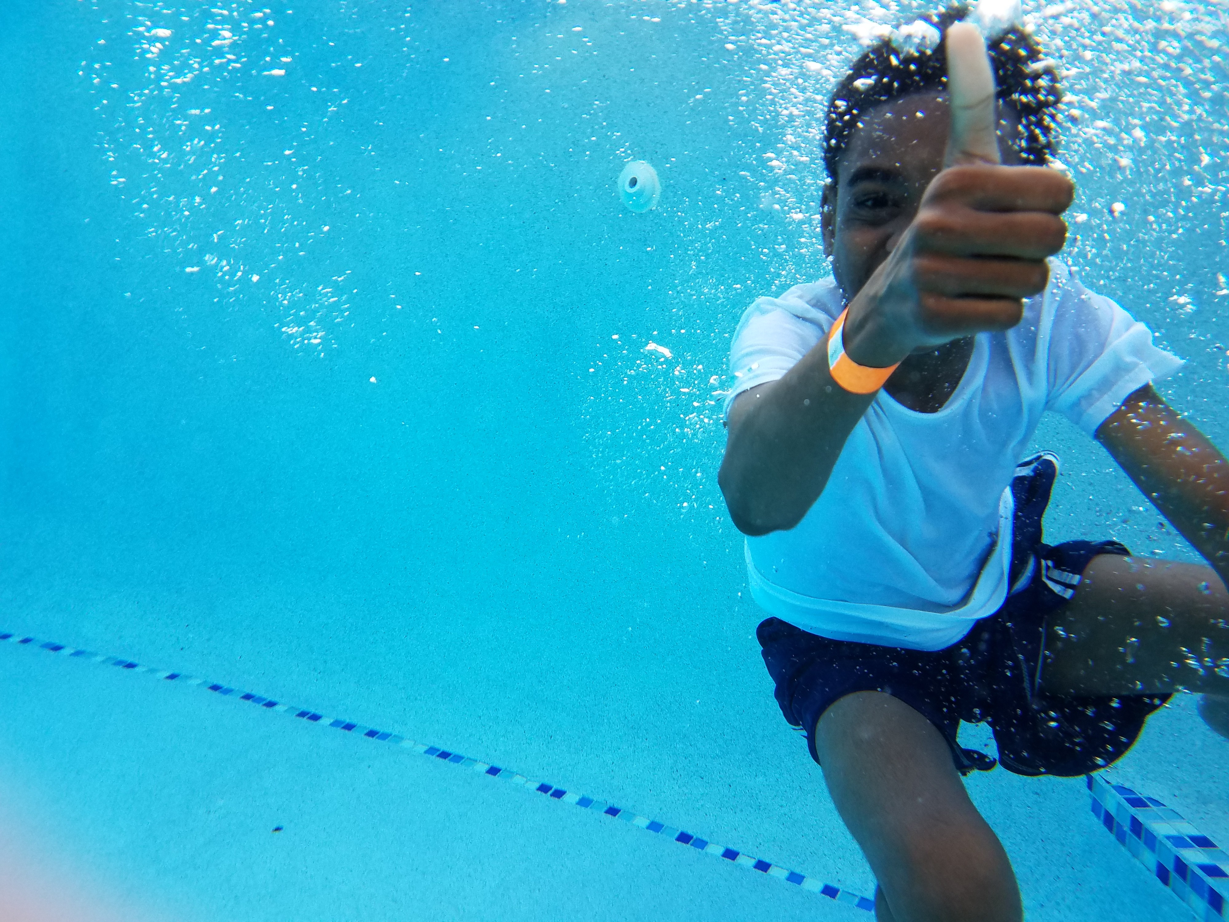 Child giving thumbs up signal underwater