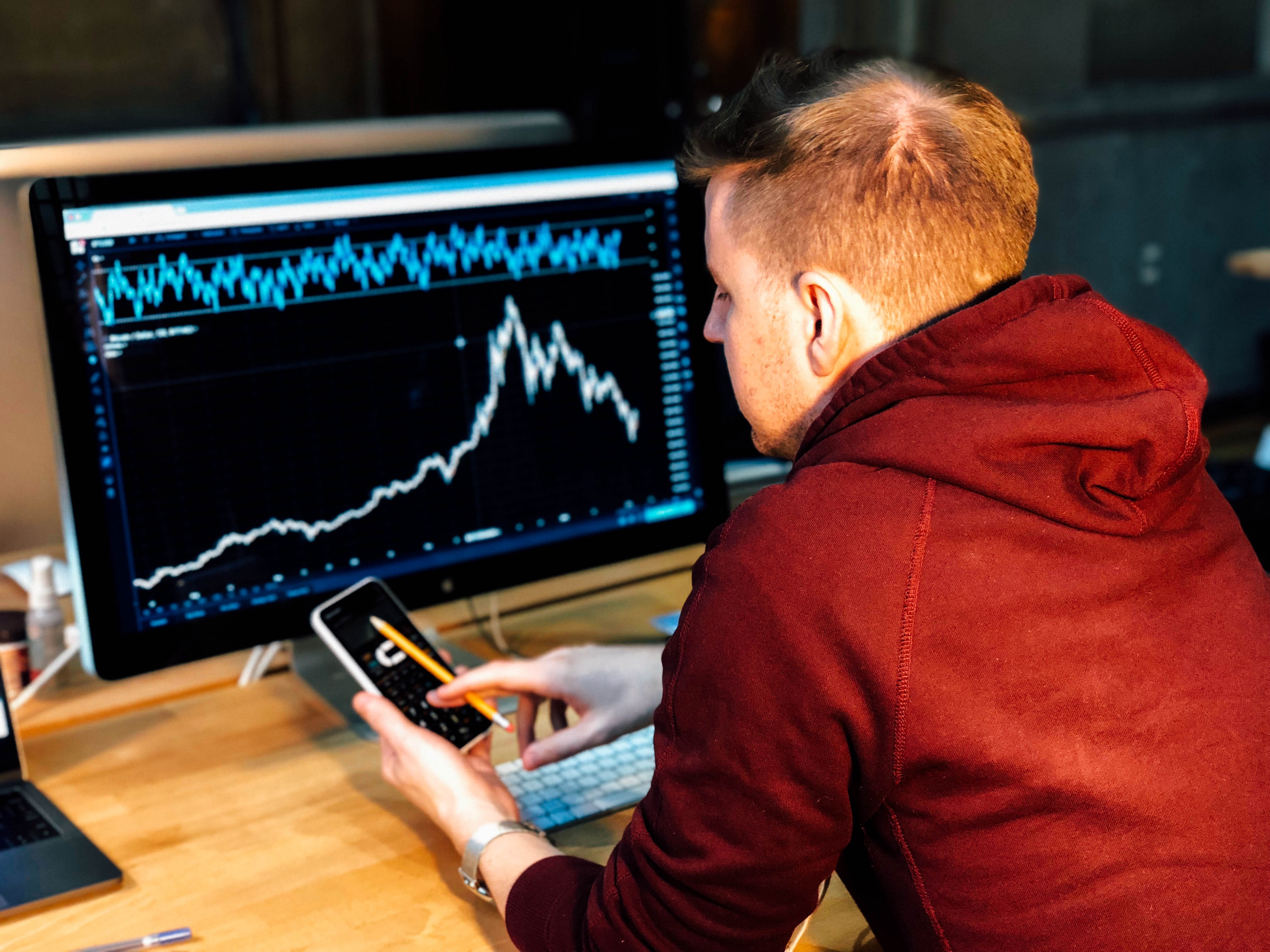 Worker sitting in front of a computer with graphs and other data on it.