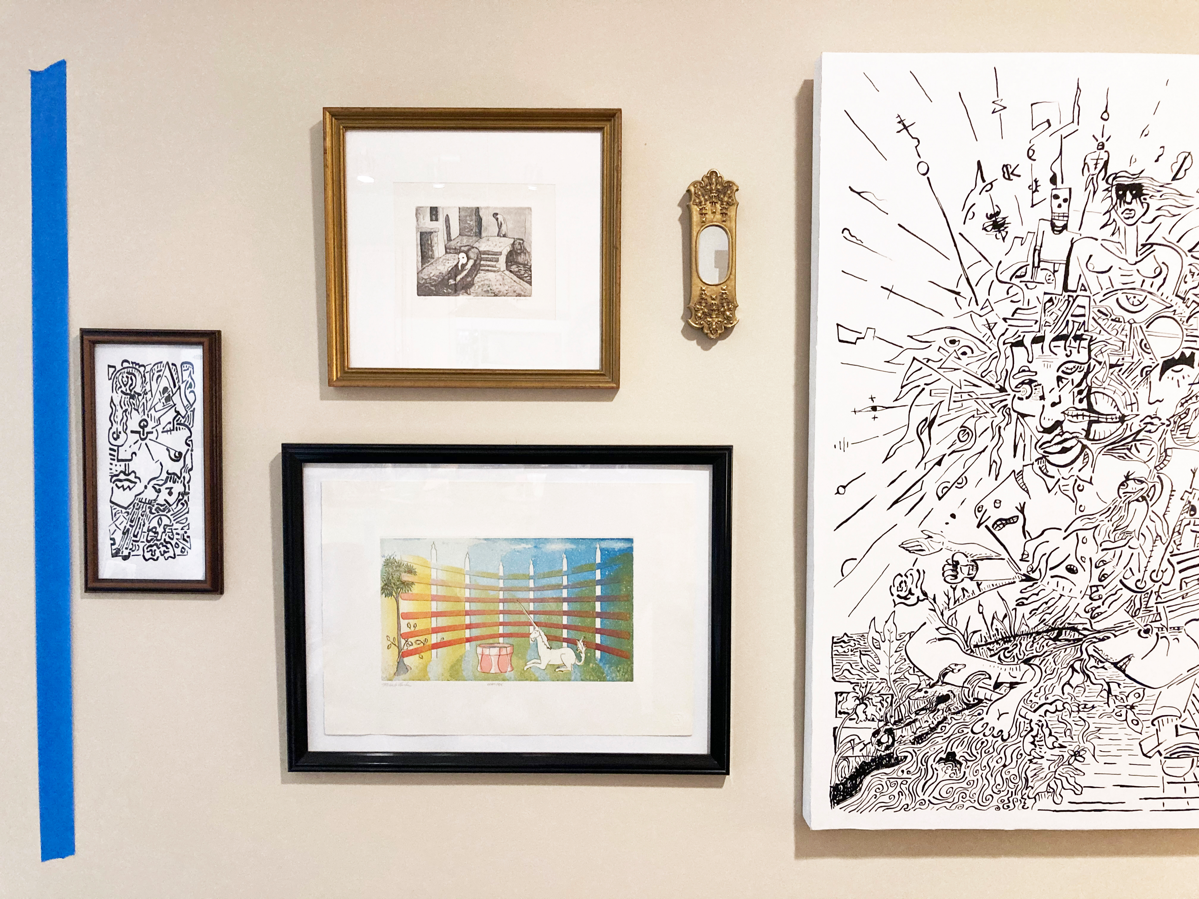 A grouping of artworks on a wall with a strip of blue painters tape on the left side.