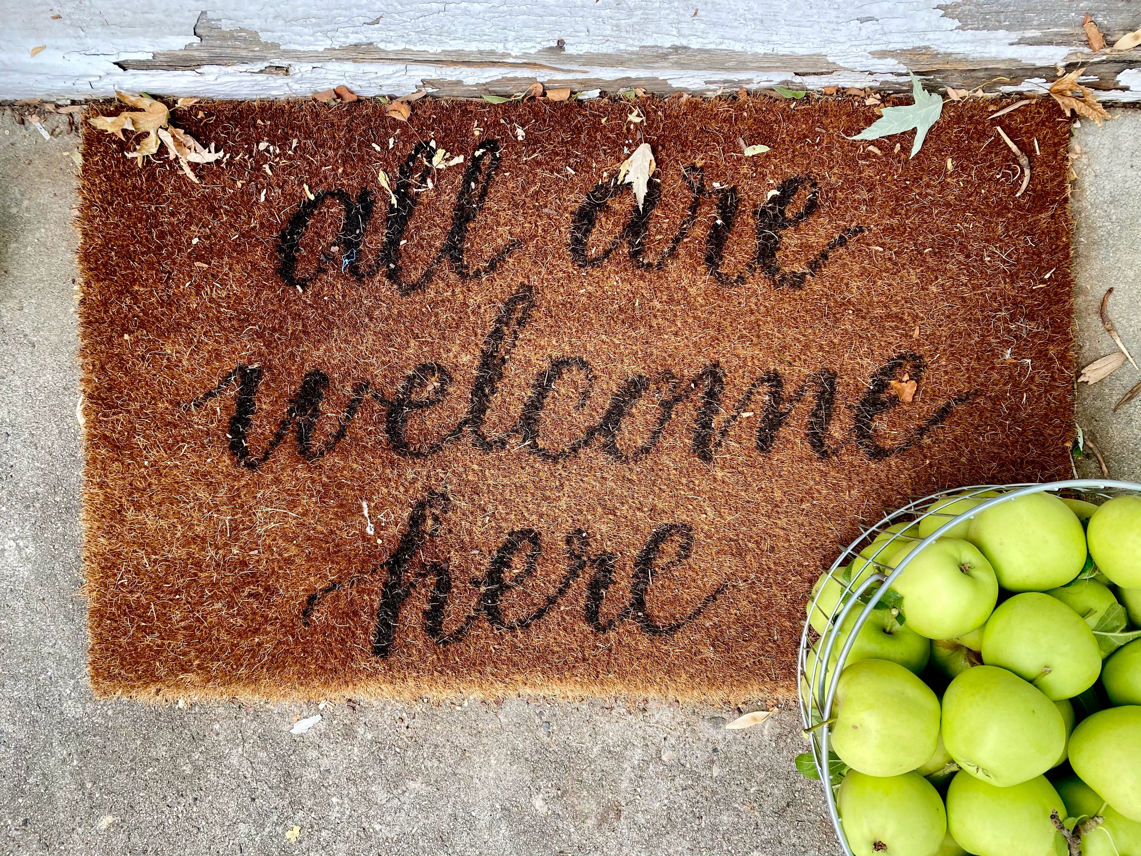 A brown doormat with a black text: 'all are welcome here'