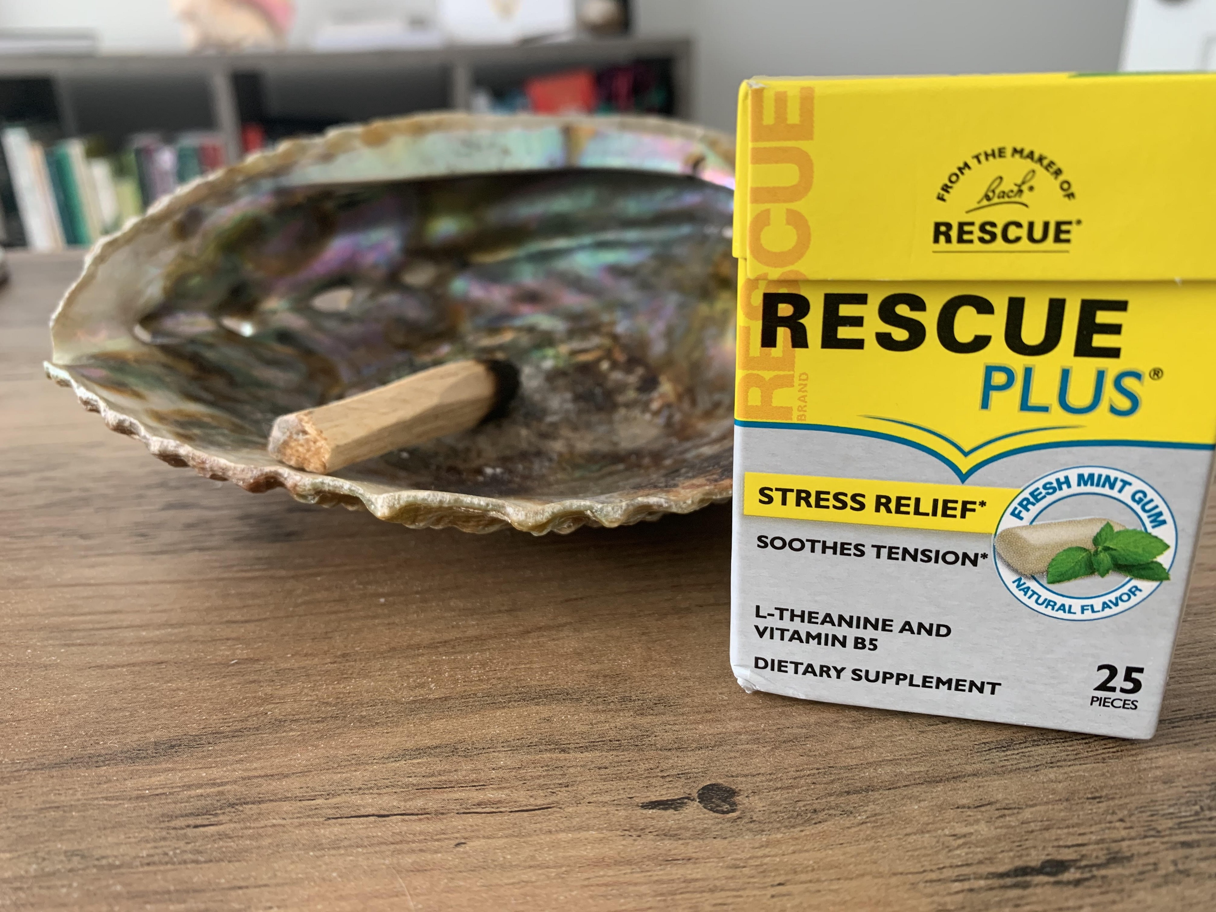 A shell with a stick of palo santo wood and a box of Bach Rescue Plus mint gum