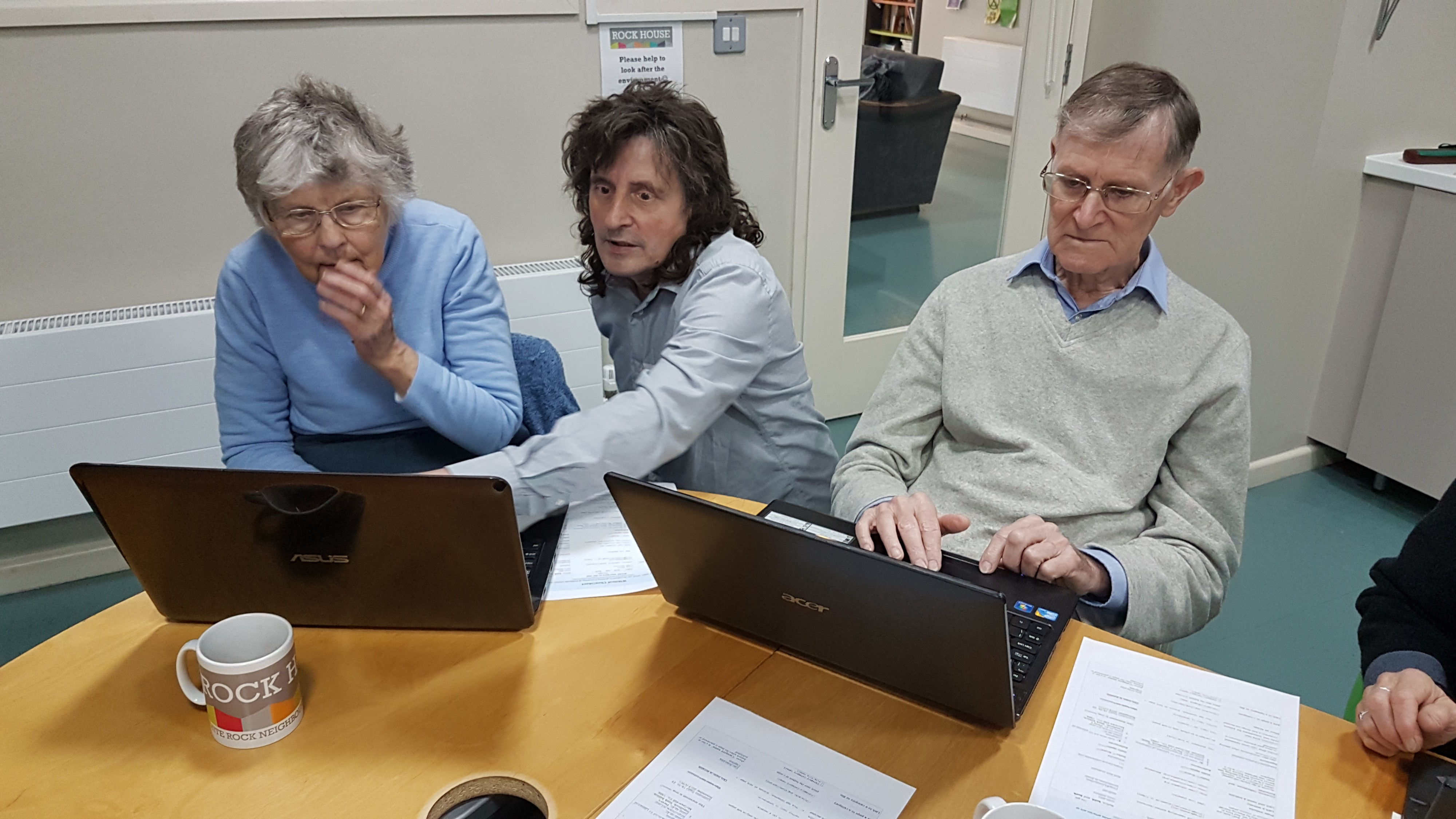 shows a man in the centre of three people looking at two laptops