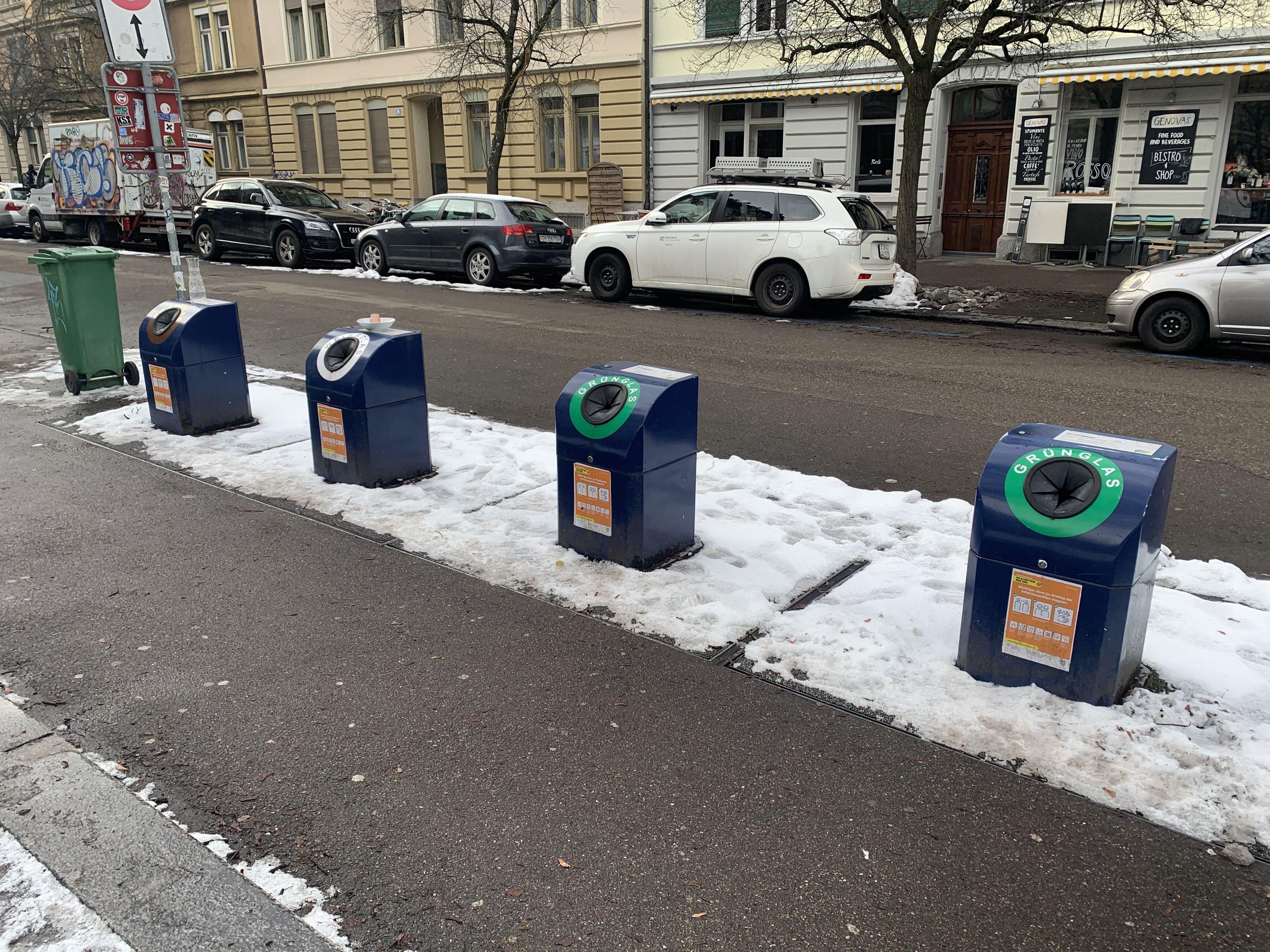 Four blue recycling bins: brown glass, white glass, and two for green glass