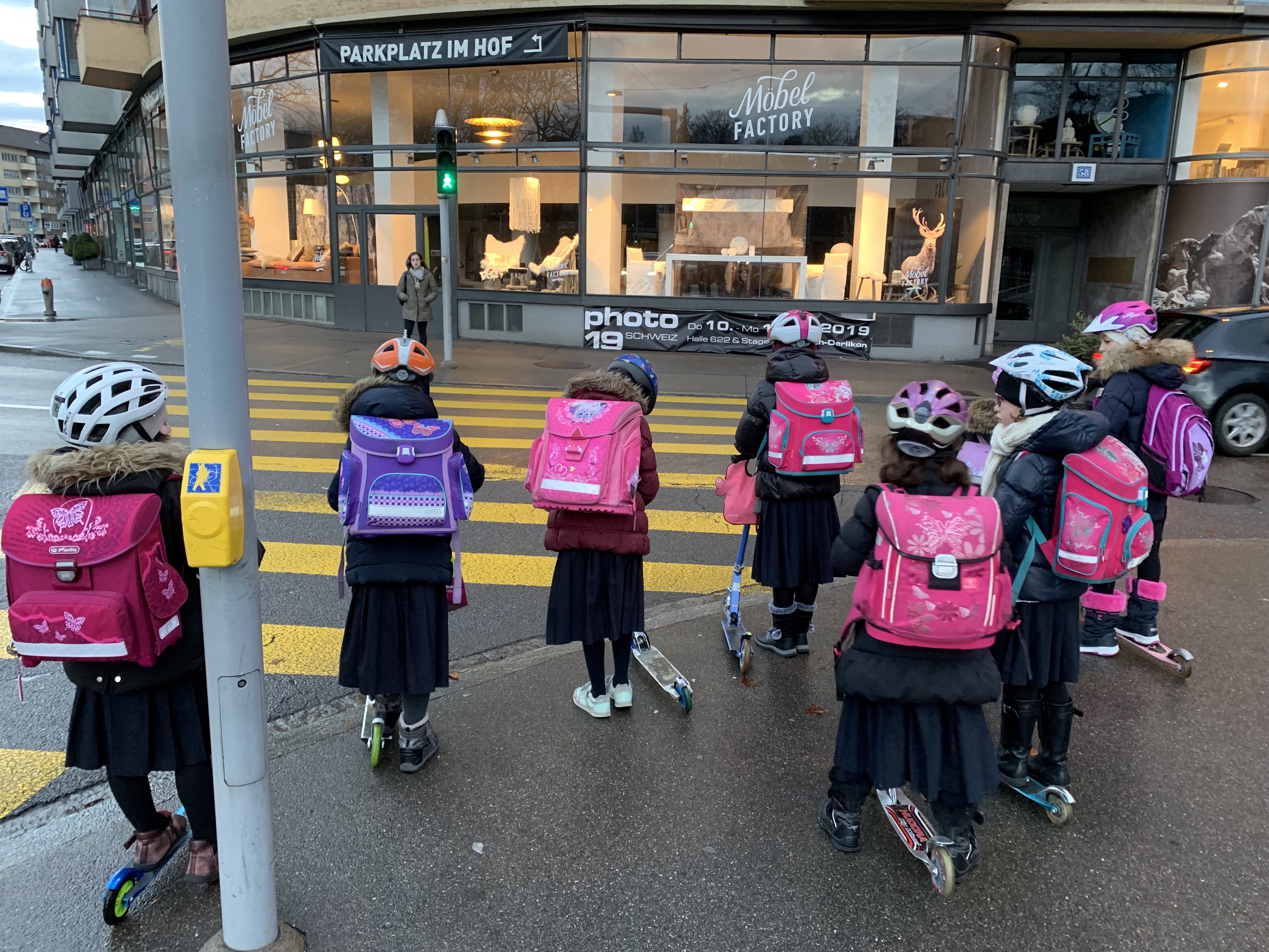 6 young girls wait to cross the street on scooters with backpacks on their way to school