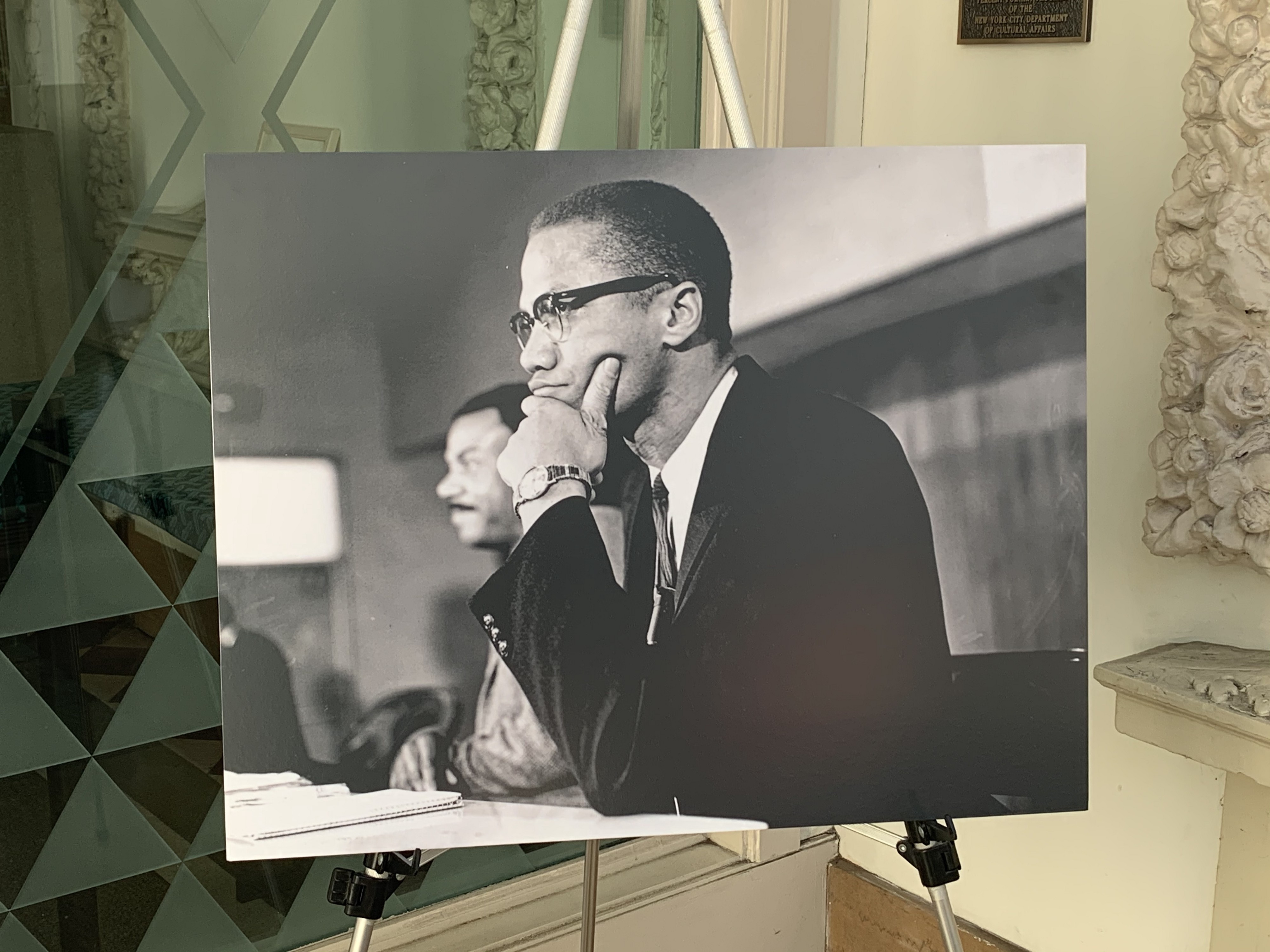 A picture of Malcolm X on an easel.
