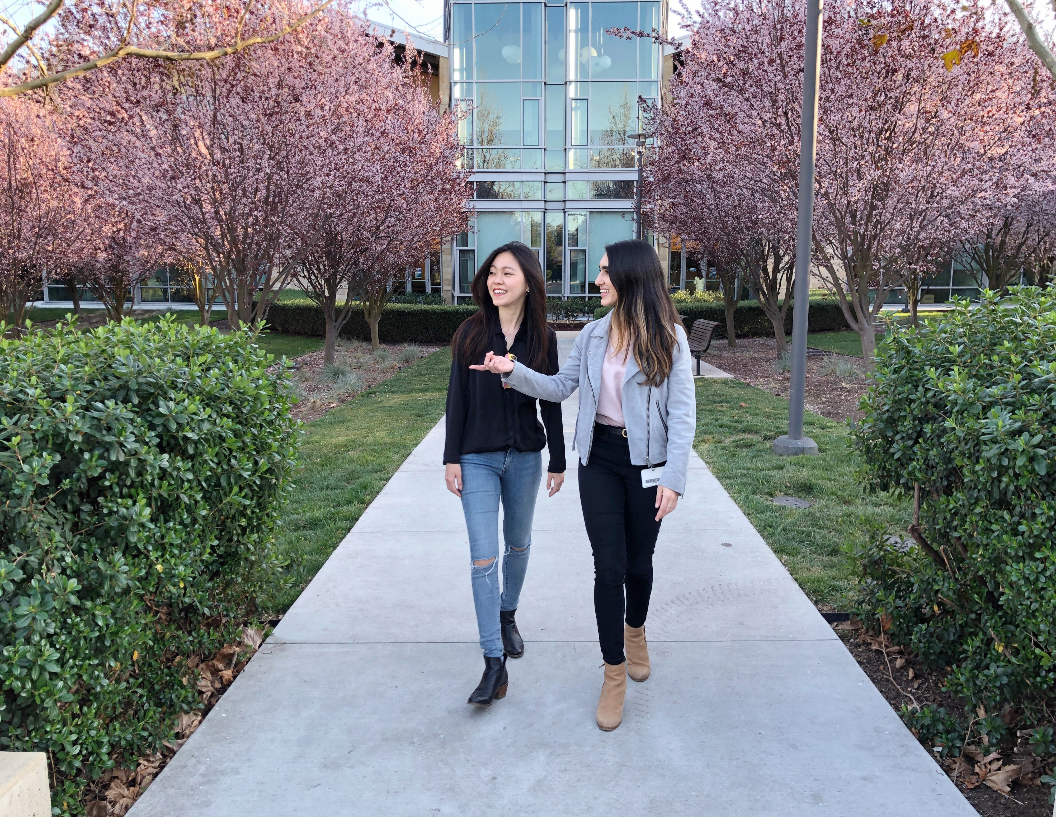 April being taken on a tour of the VMware campus by a designer on the team, with cherry blossom trees along a pathway