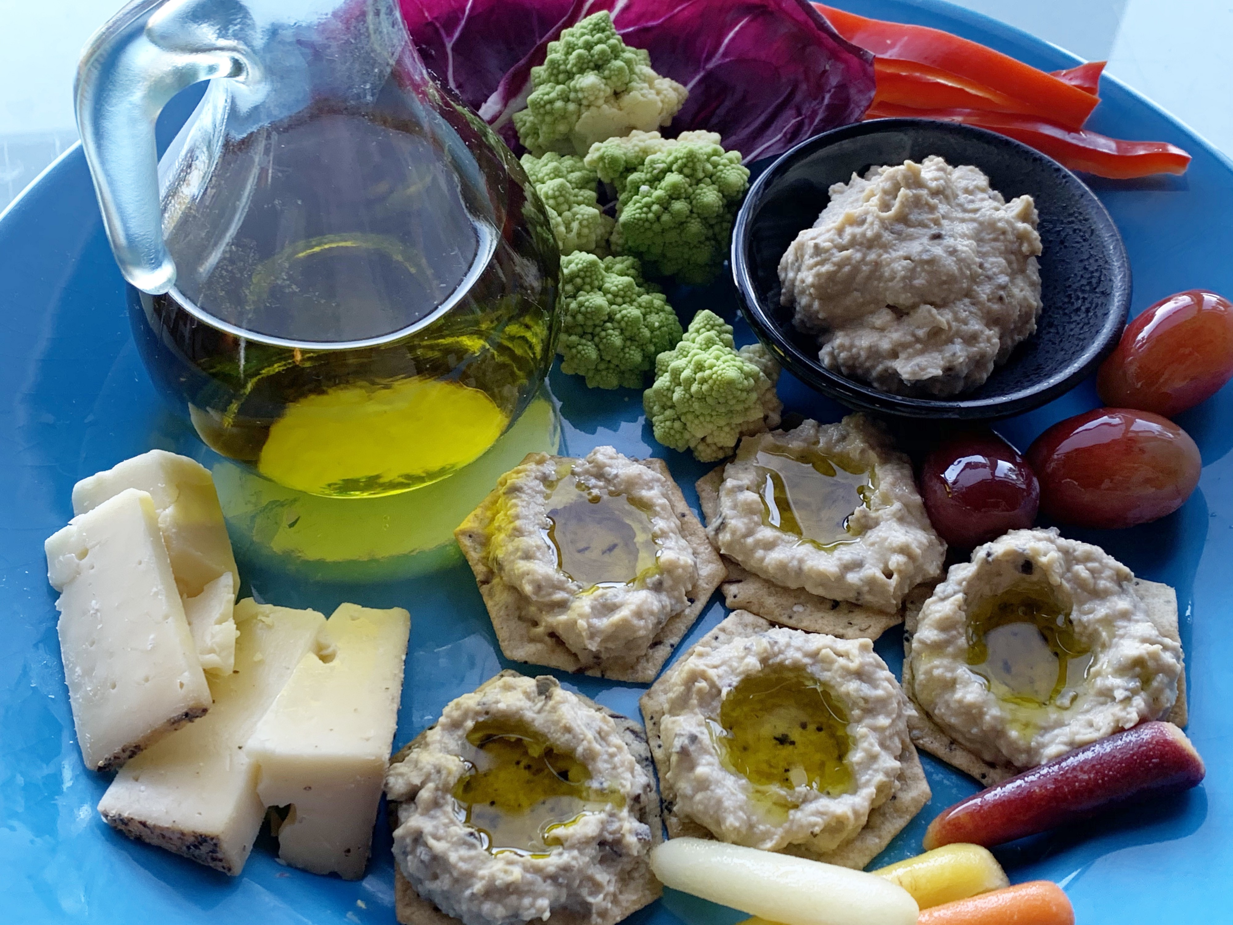 Snack of olive oil, hummus, crackers, and vegetables