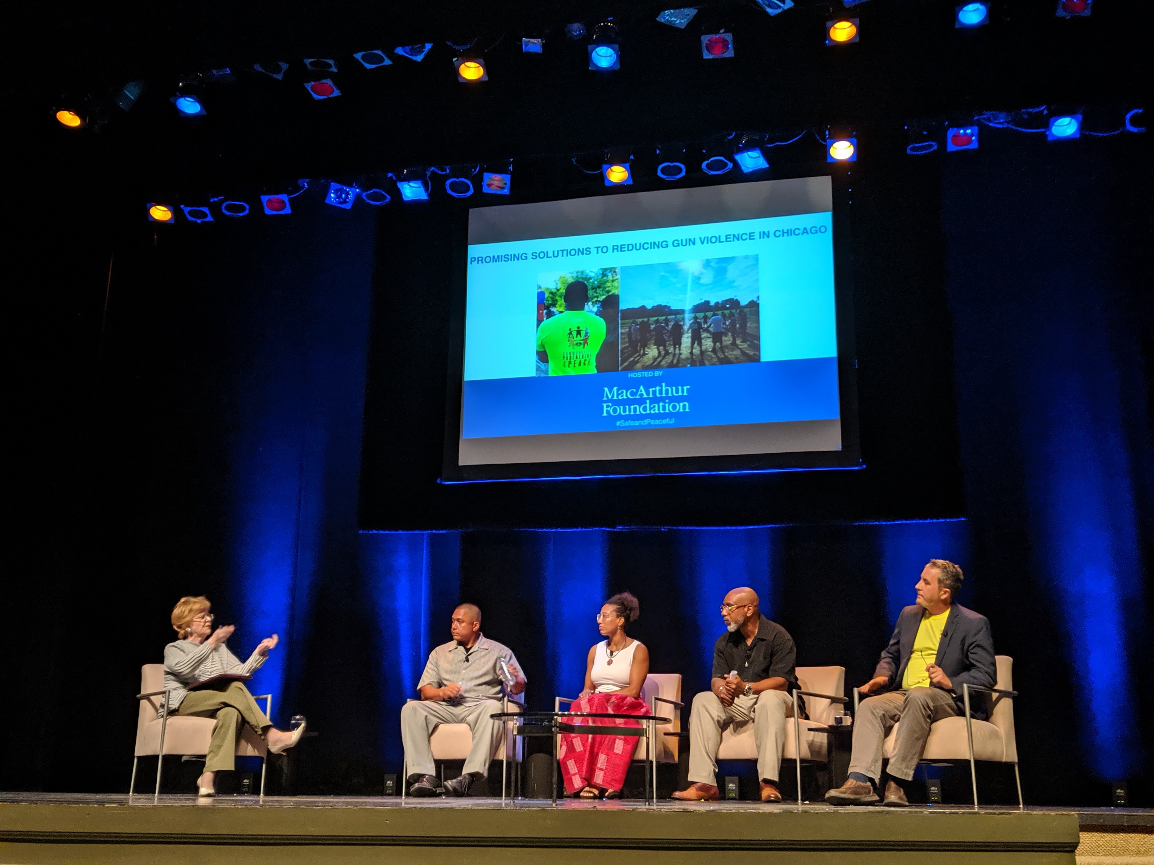 Panelists sit on stage. From left to right: Julia Stasch, Jorge Matos, Tanya Woods, Billy Moore, and Teny Gross.
