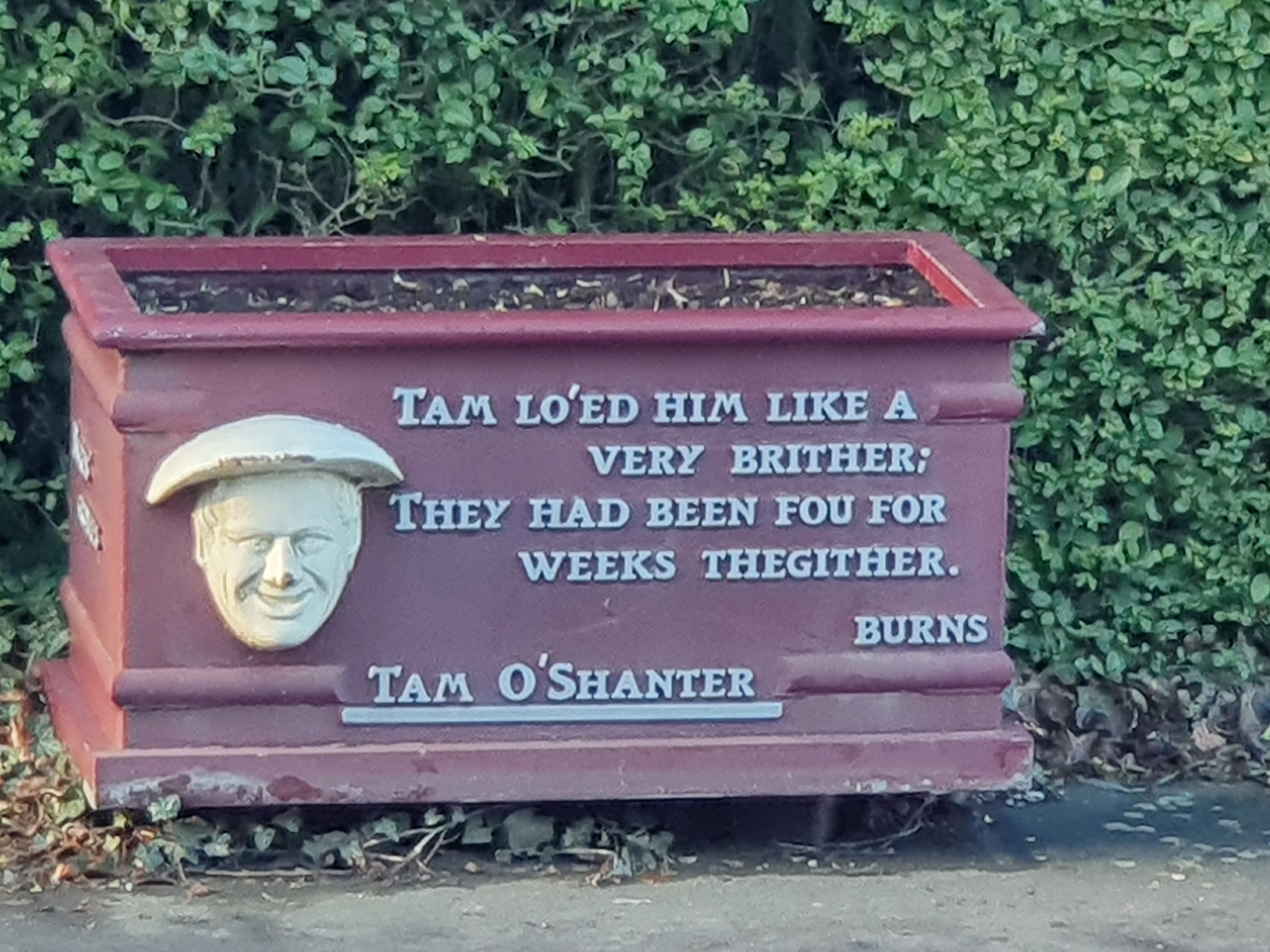 This is a picture of a red Plant Box sitting on the pavement outside Burns Cottage. The box is red and has a white outline of an old man and an inscription dedicated to Tam O Shanter