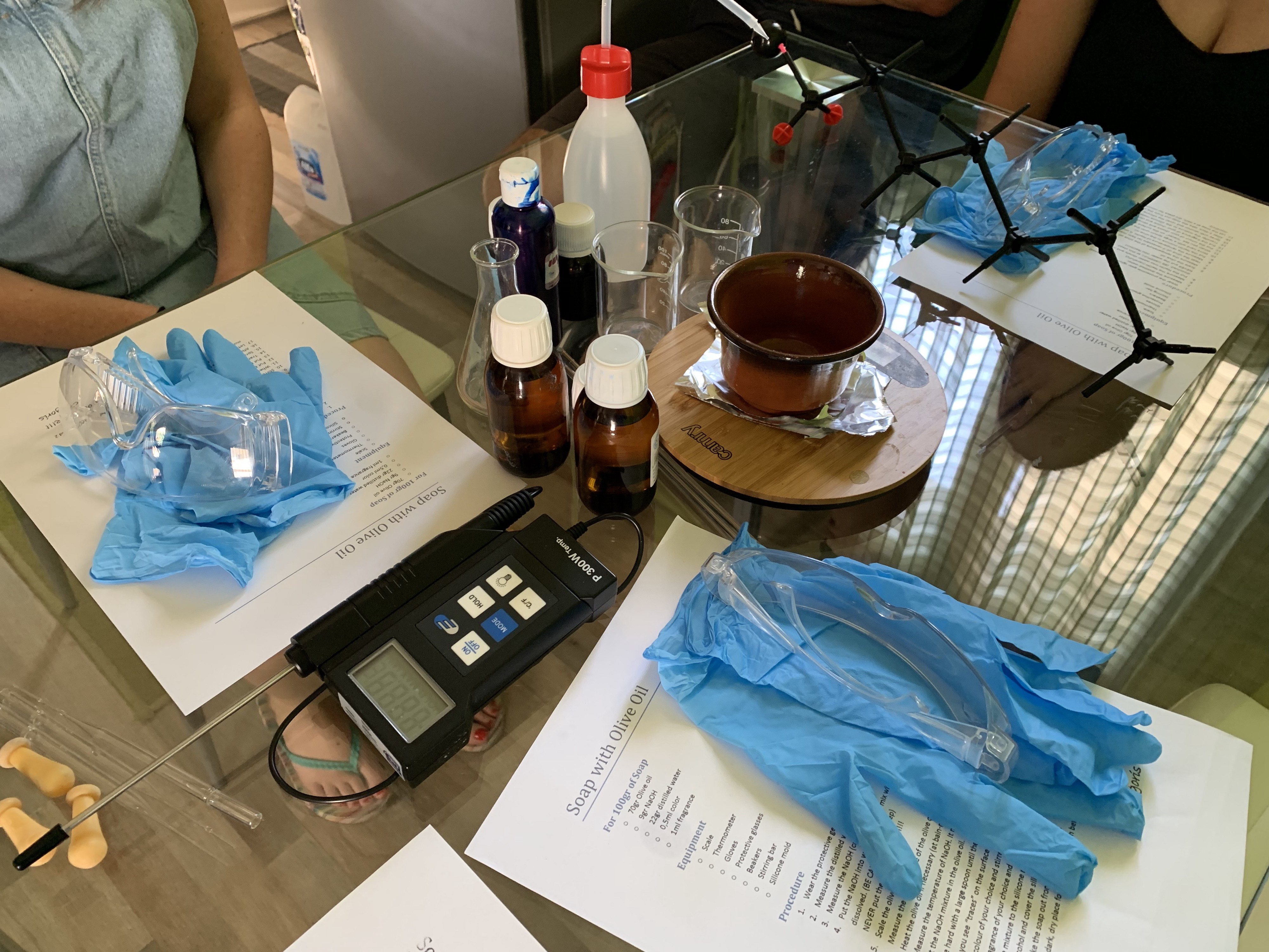 Gloves, goggles, a digital thermometer, and bottles of liquid