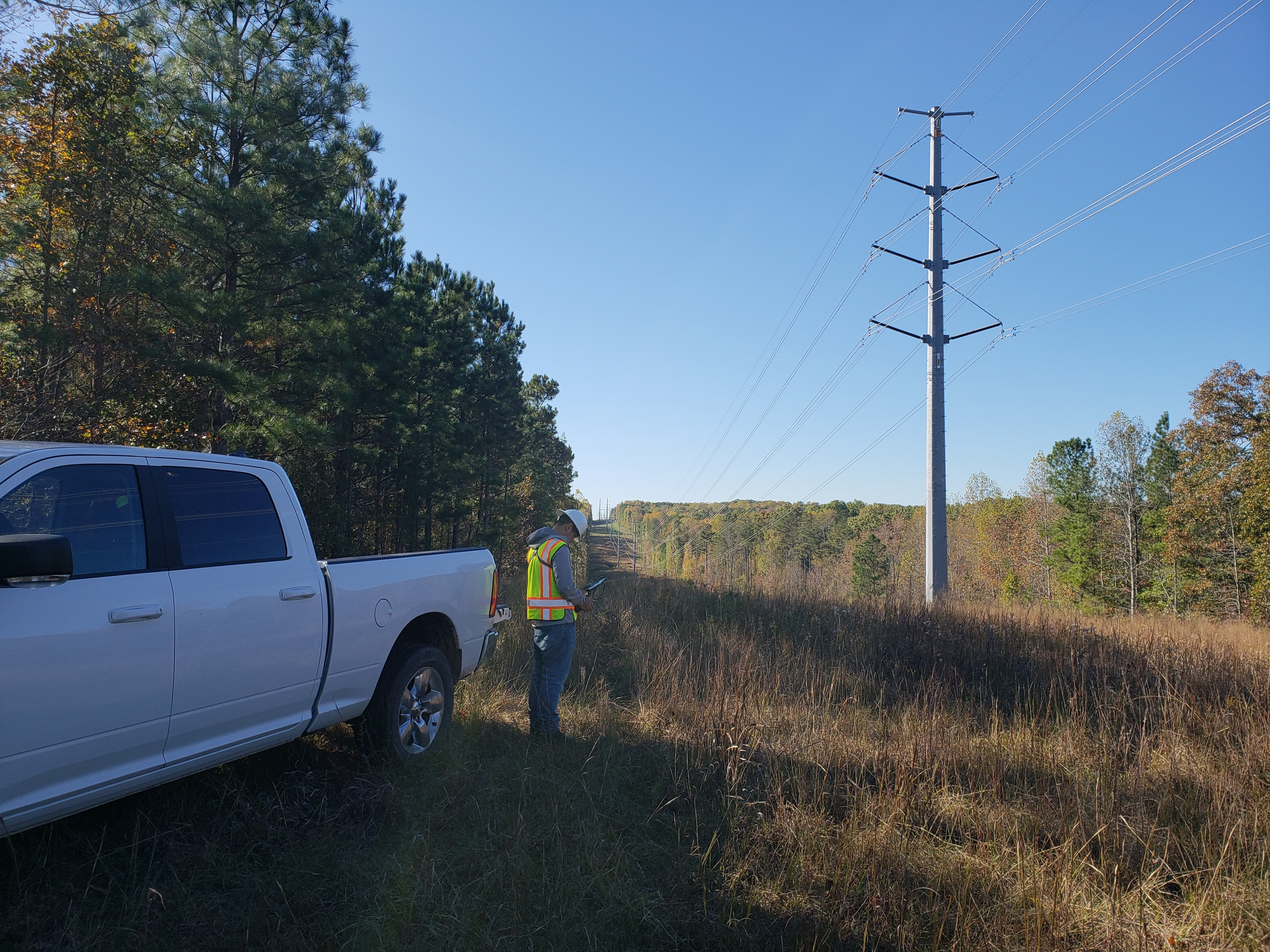 Drone operator performs field inspection of powerlines