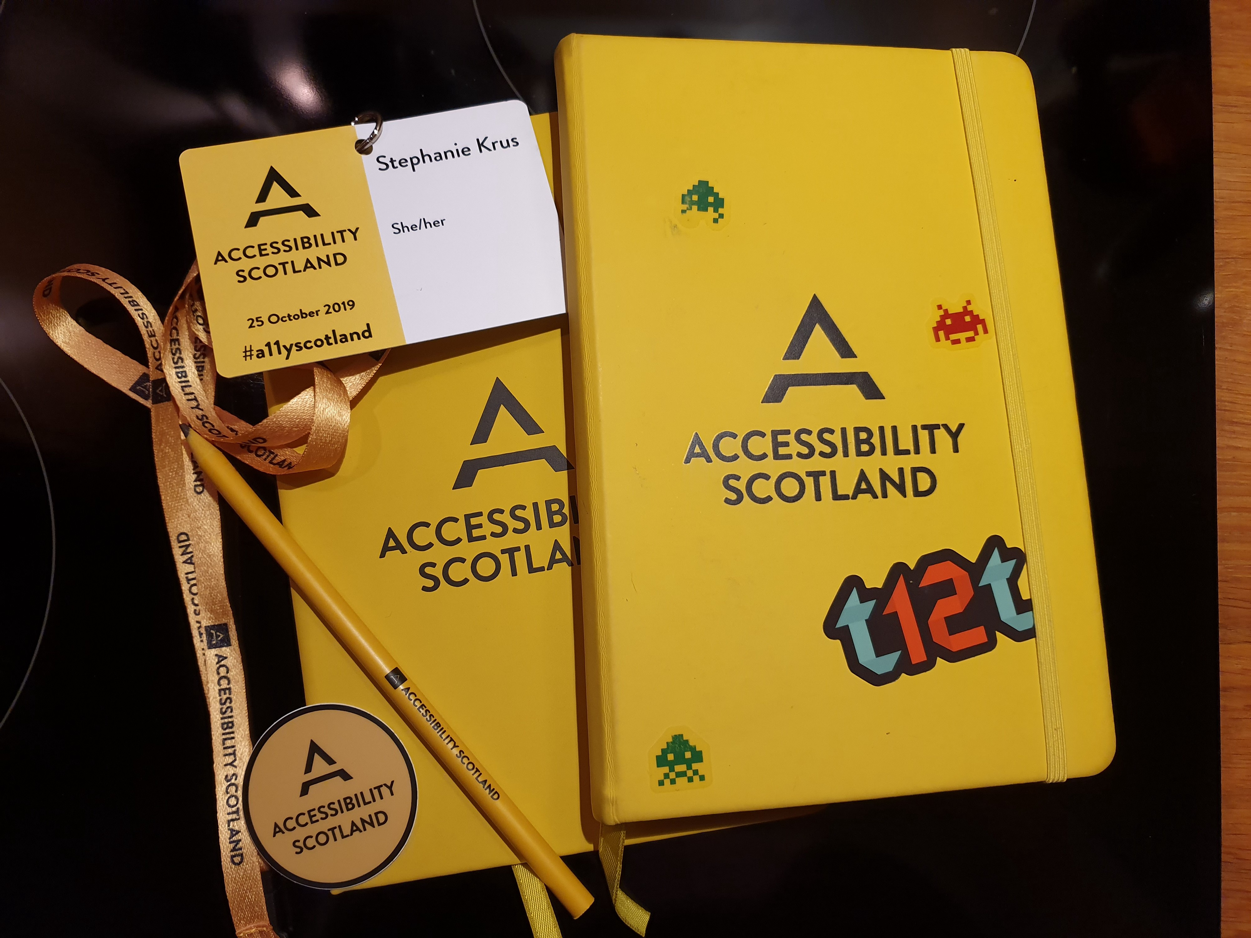 2 notepads (one from last year) a sticker, a pencil,  all with Accessibility Scotland branding and my name badge