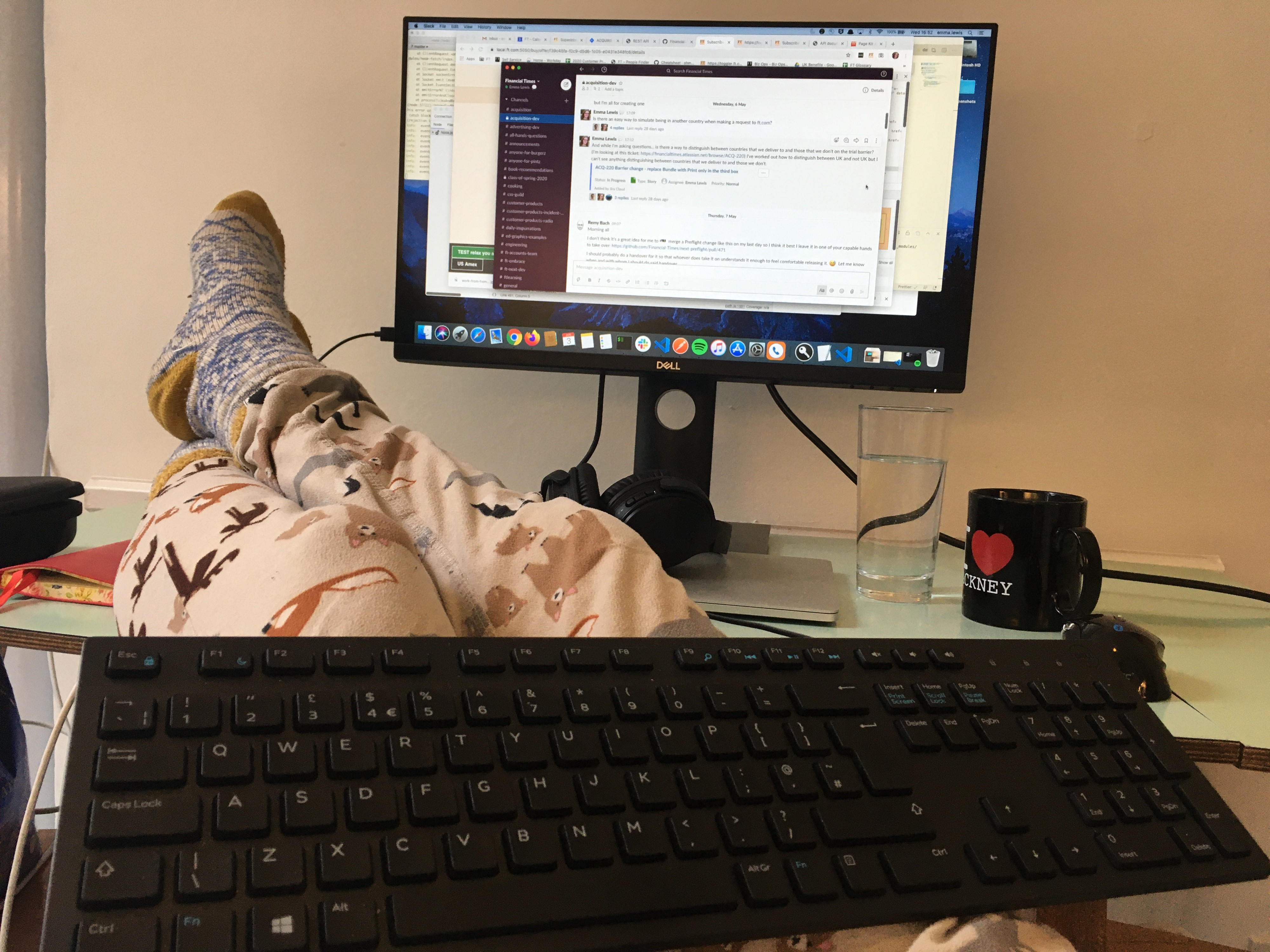 Feet up on a desk, wearing pyjama bottoms, keyboard on lap and Slack on screen.