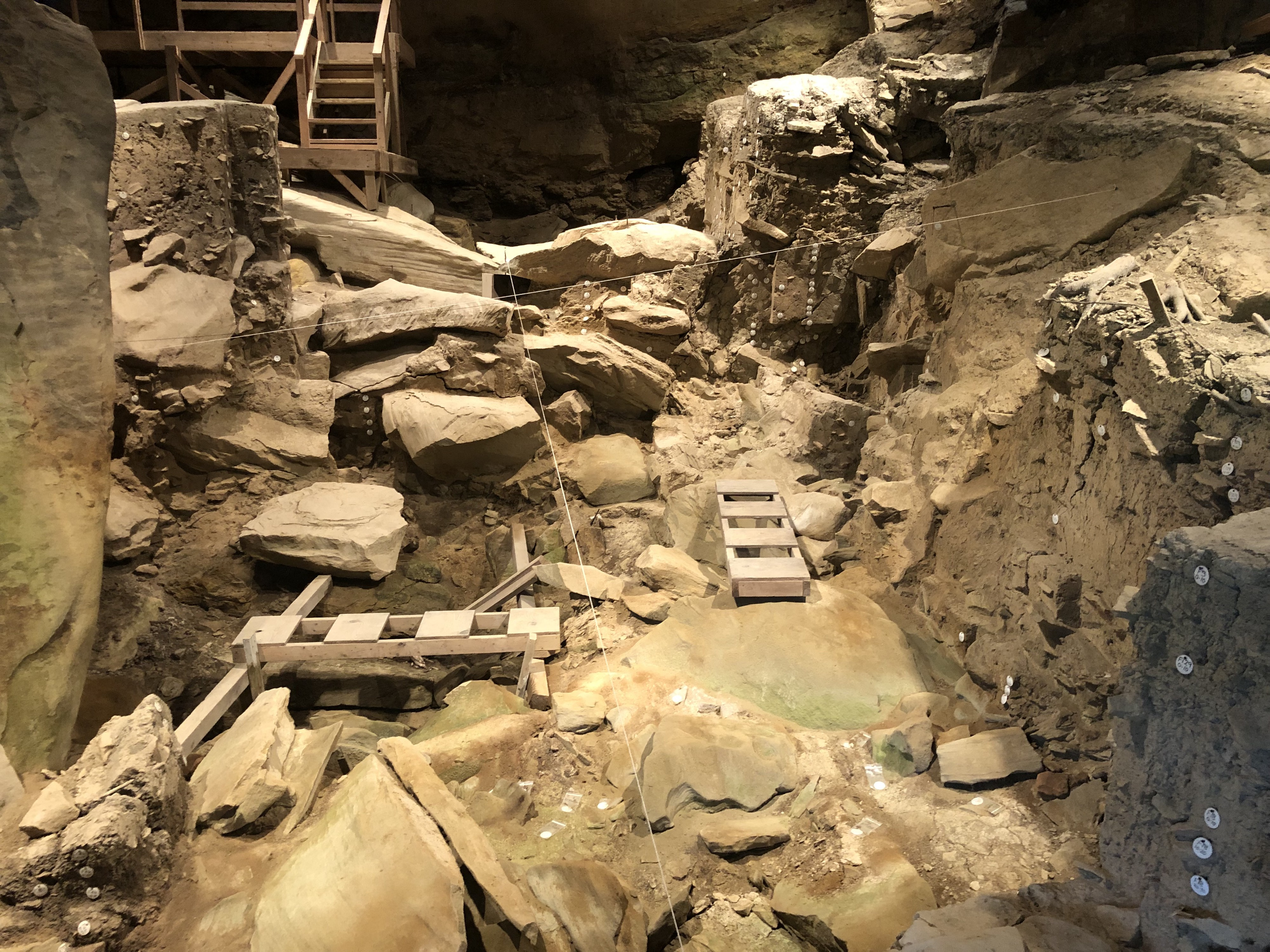 The interior of the Meadowcroft Rockshelter in Avella, Pennsylvania. This site features an archaeological dig preserved as it was left after the dig was completed in the late 1970s. Small tags dot the stones indicating strata. Wooden ladders and walkways are present, allowing for access to harder to get to portions of the dig site. Photo by Mike Luoma.