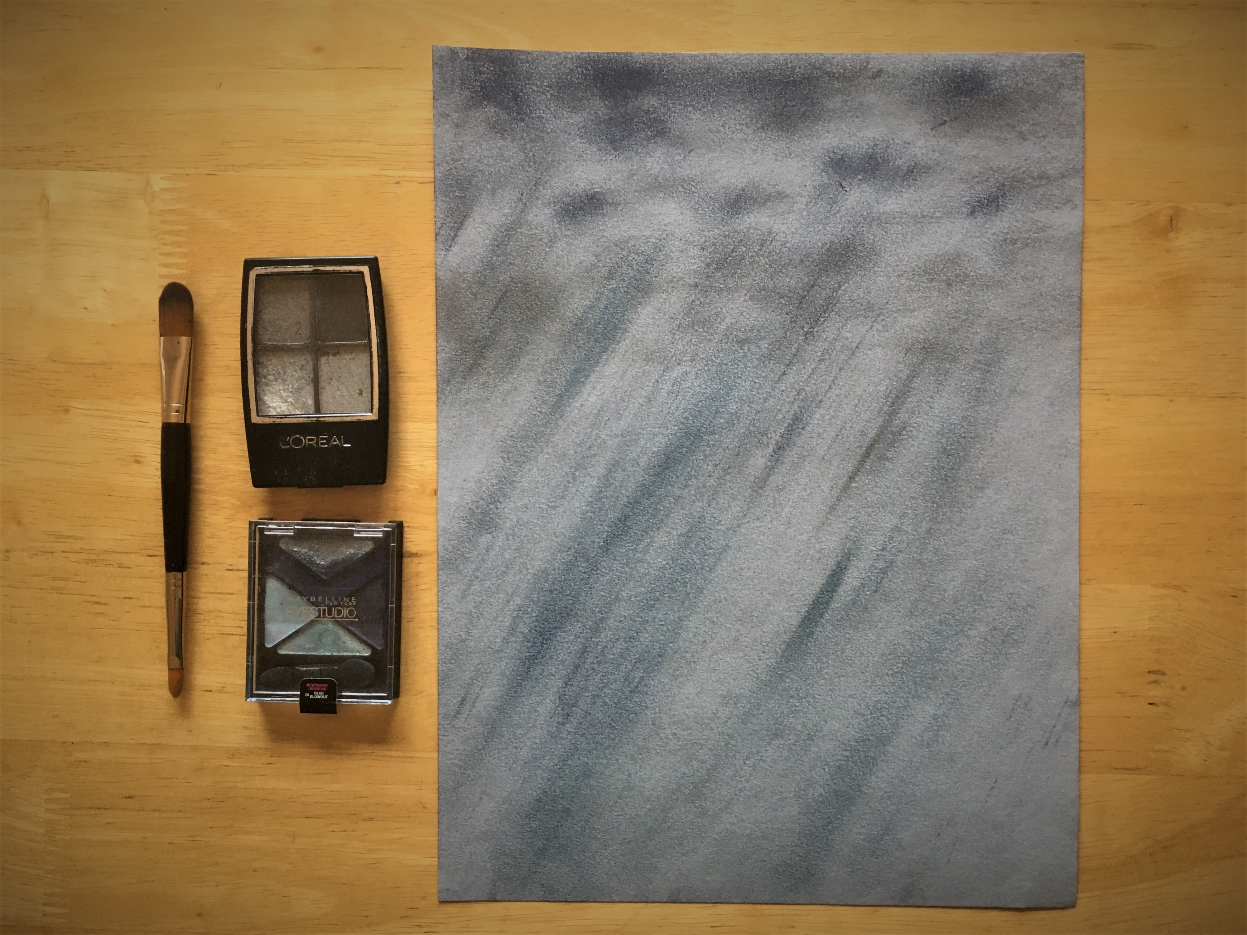 """Eyeshadow palettes sit alongside a """"drawing"""" of gray clouds and driving blue rain, created with the makeup."""