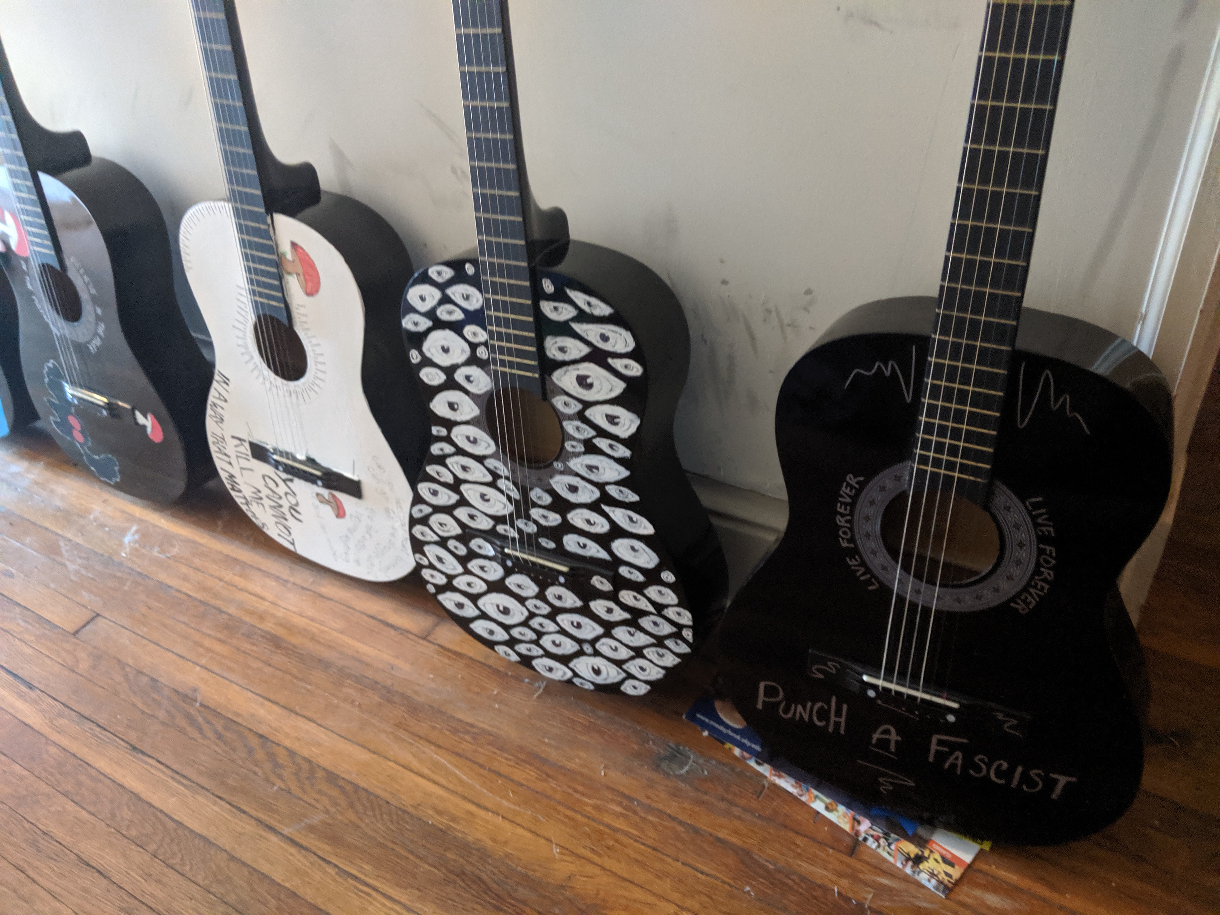 a collection of painted guitars lined up against a wall.