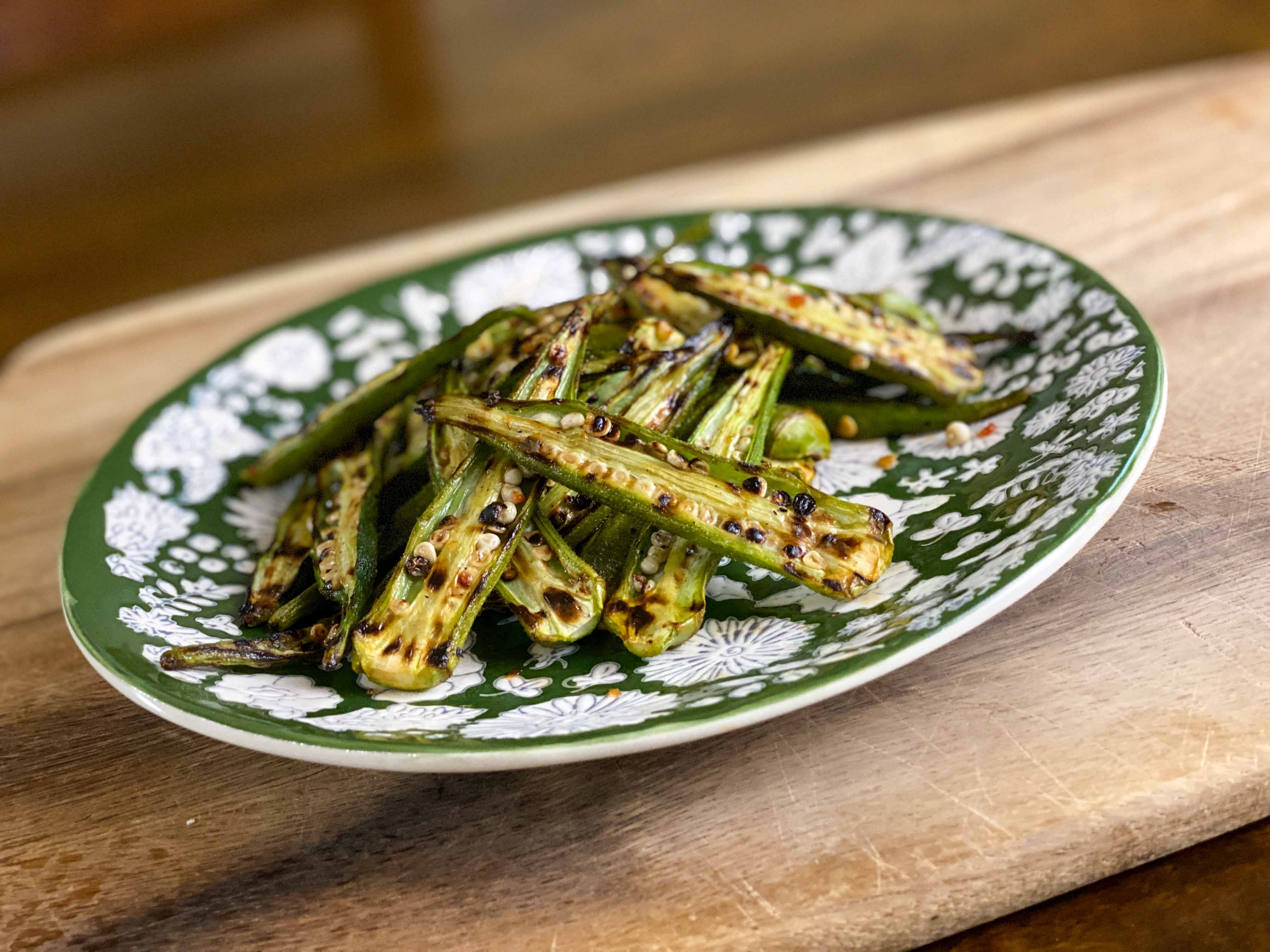 Charred okra, made on a stovetop grill or griddle, on a green-and-white plate. The recipe is from Cooks Without Borders.
