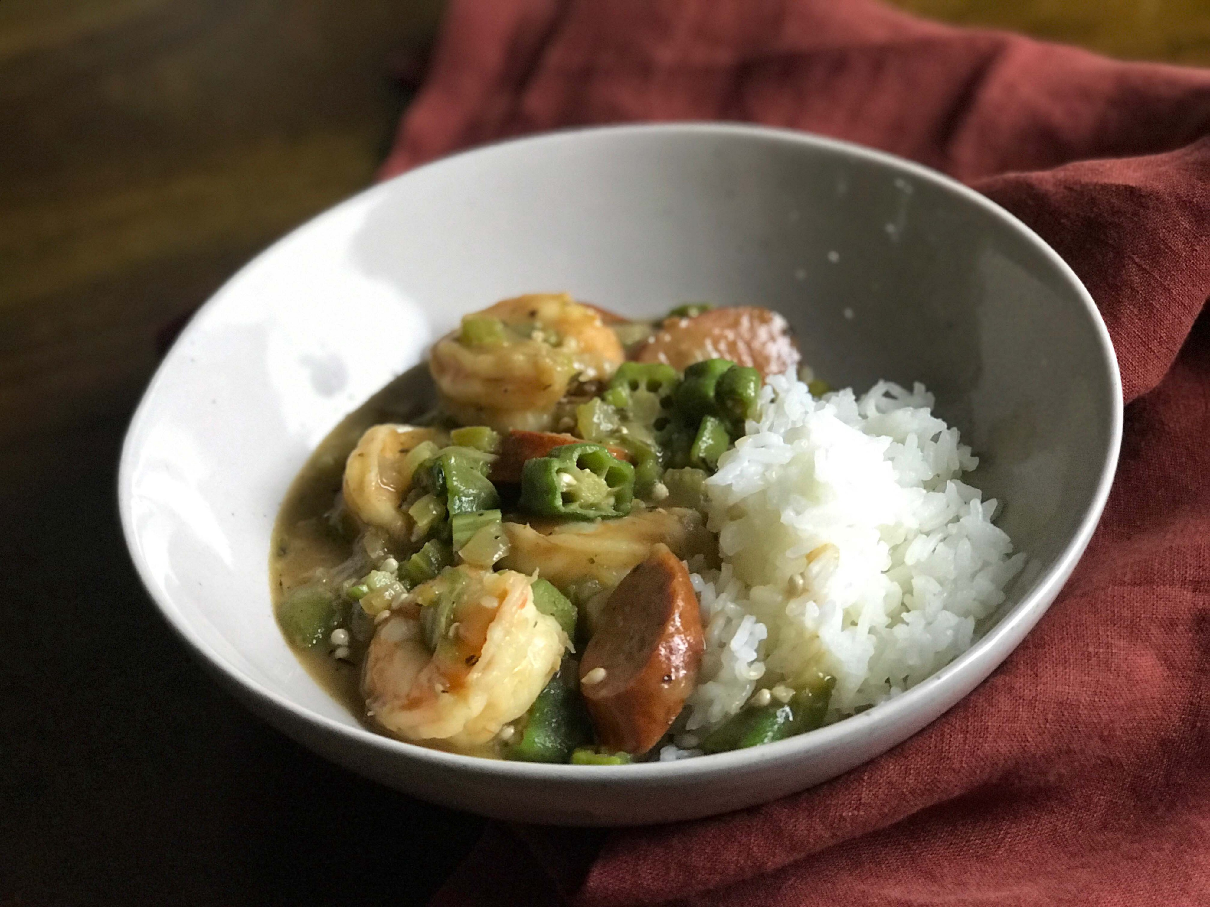 Shrimp, andouille sausage and okra gumbo with white rice, served in a white bowl. The recipe is from Cooks Without Borders.