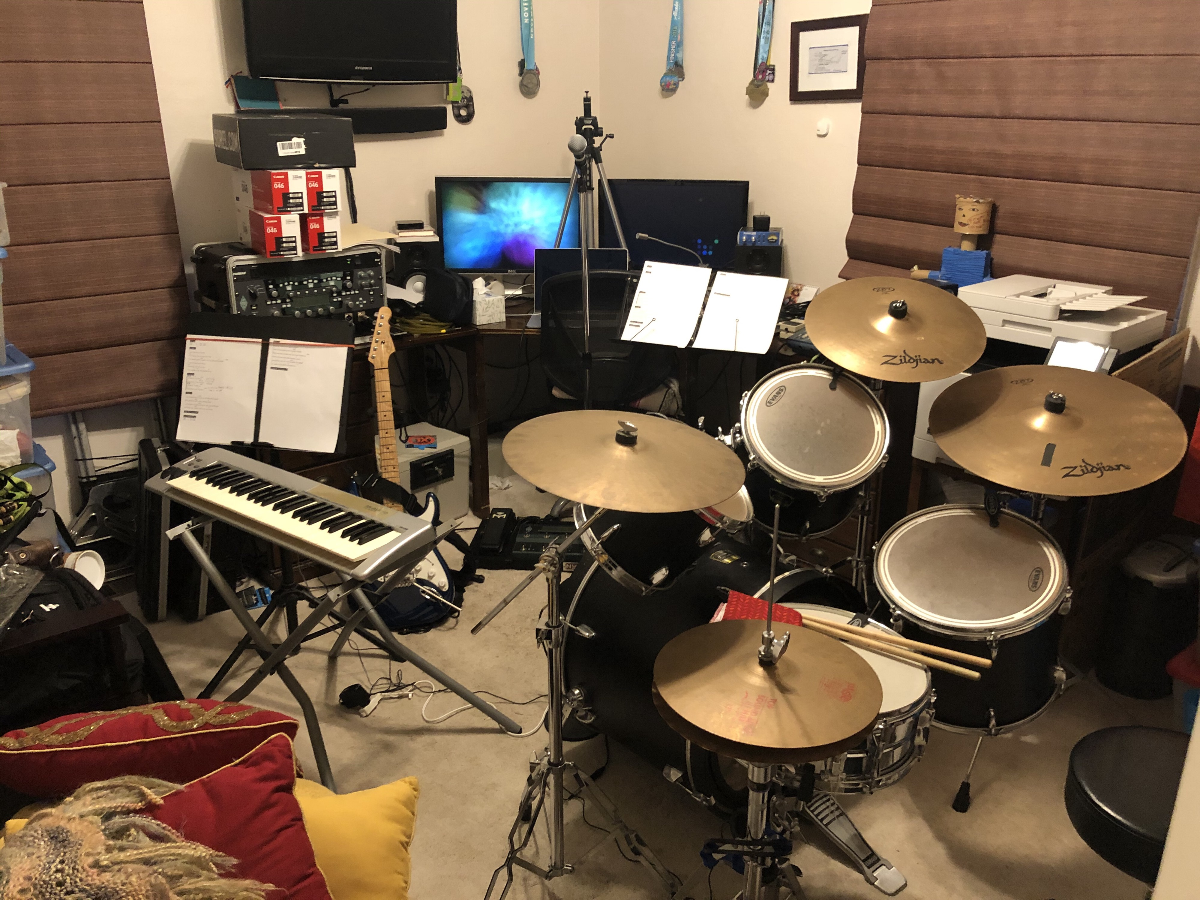 Drums, keyboard, guitar, camera, and computer fit into small room.