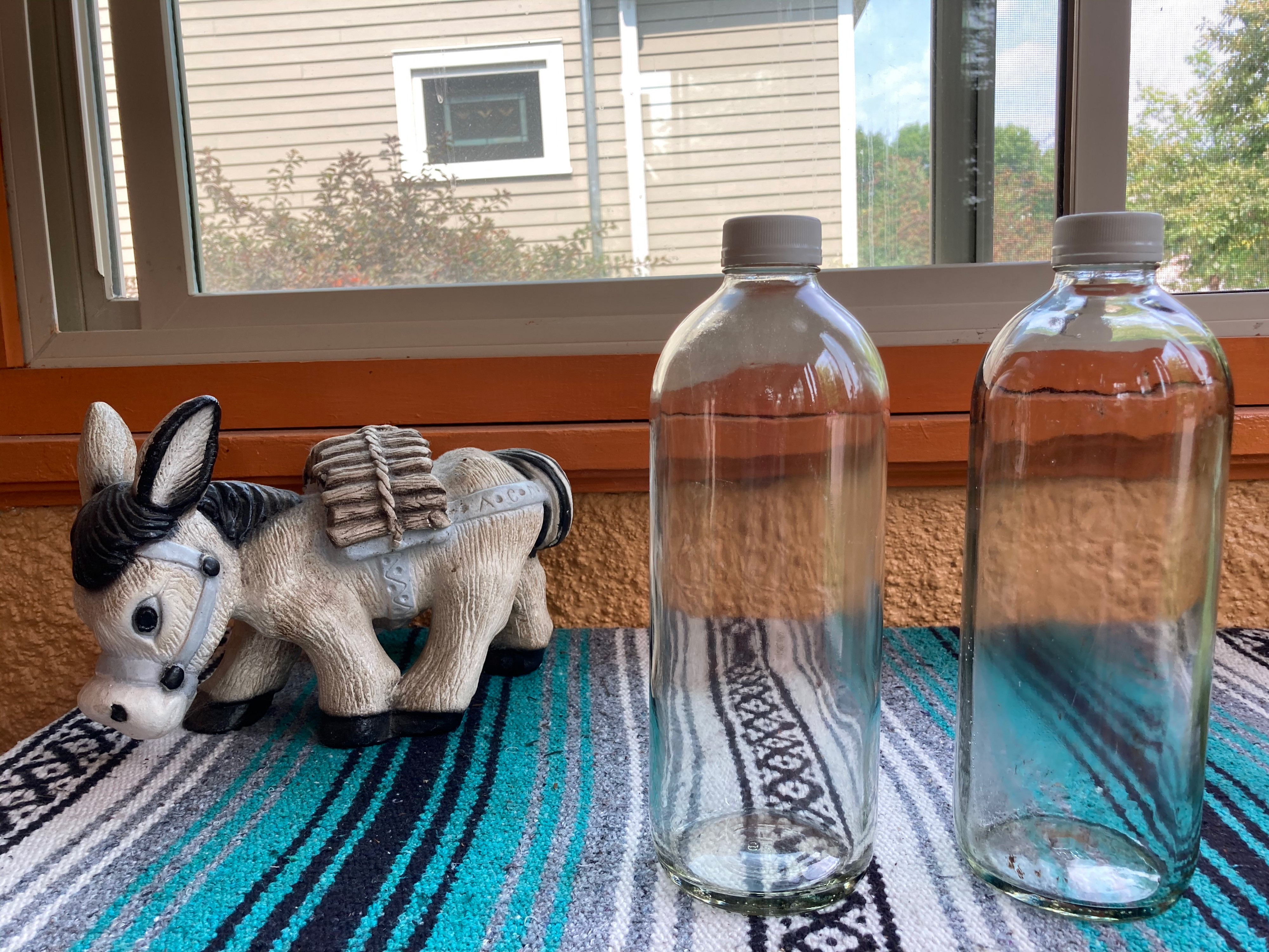 2 48-ounce bottles used for water, with a donkey for scale.