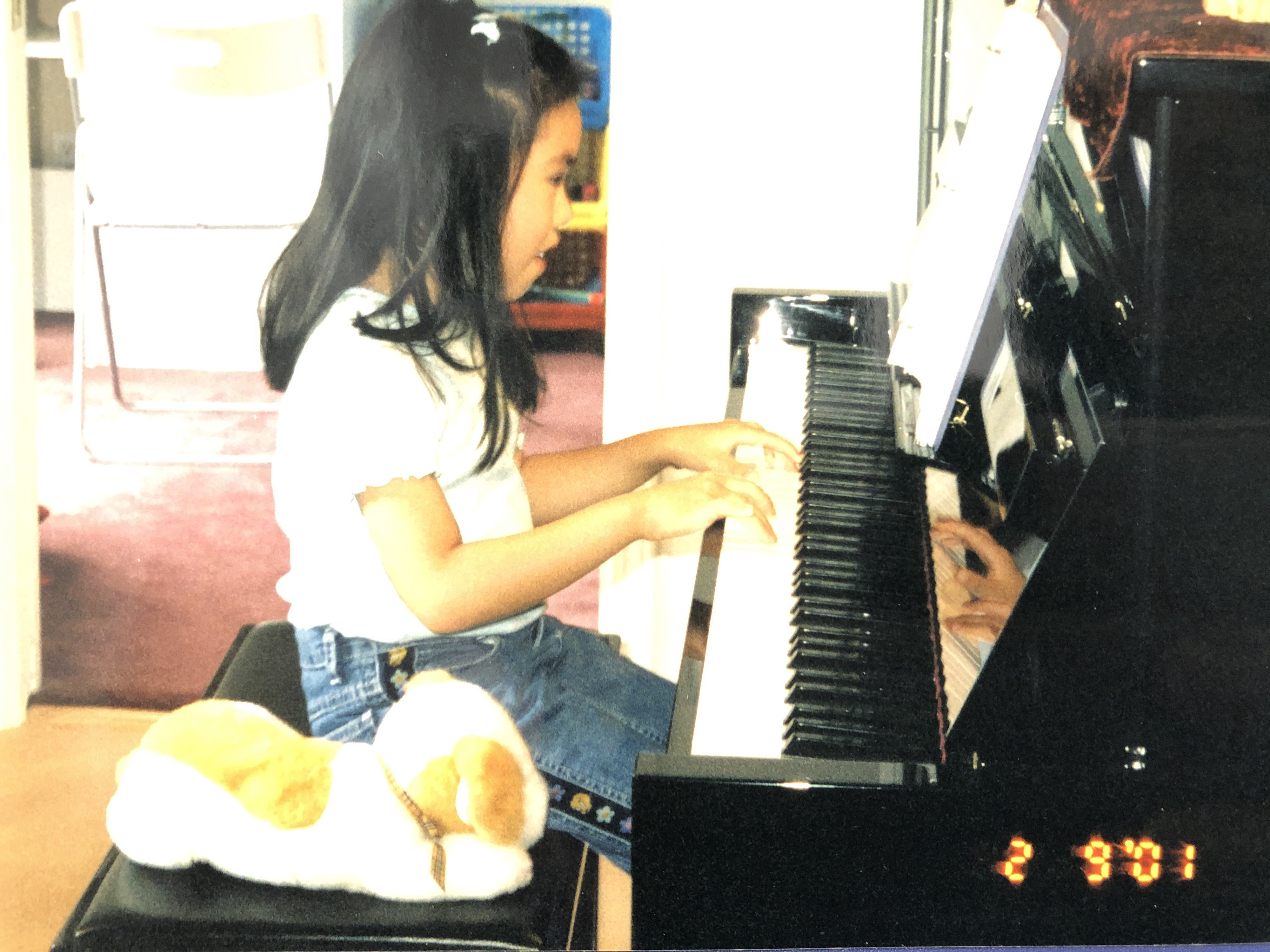 Young girl playing piano with white and orange stuffed dog next to her on the bench.