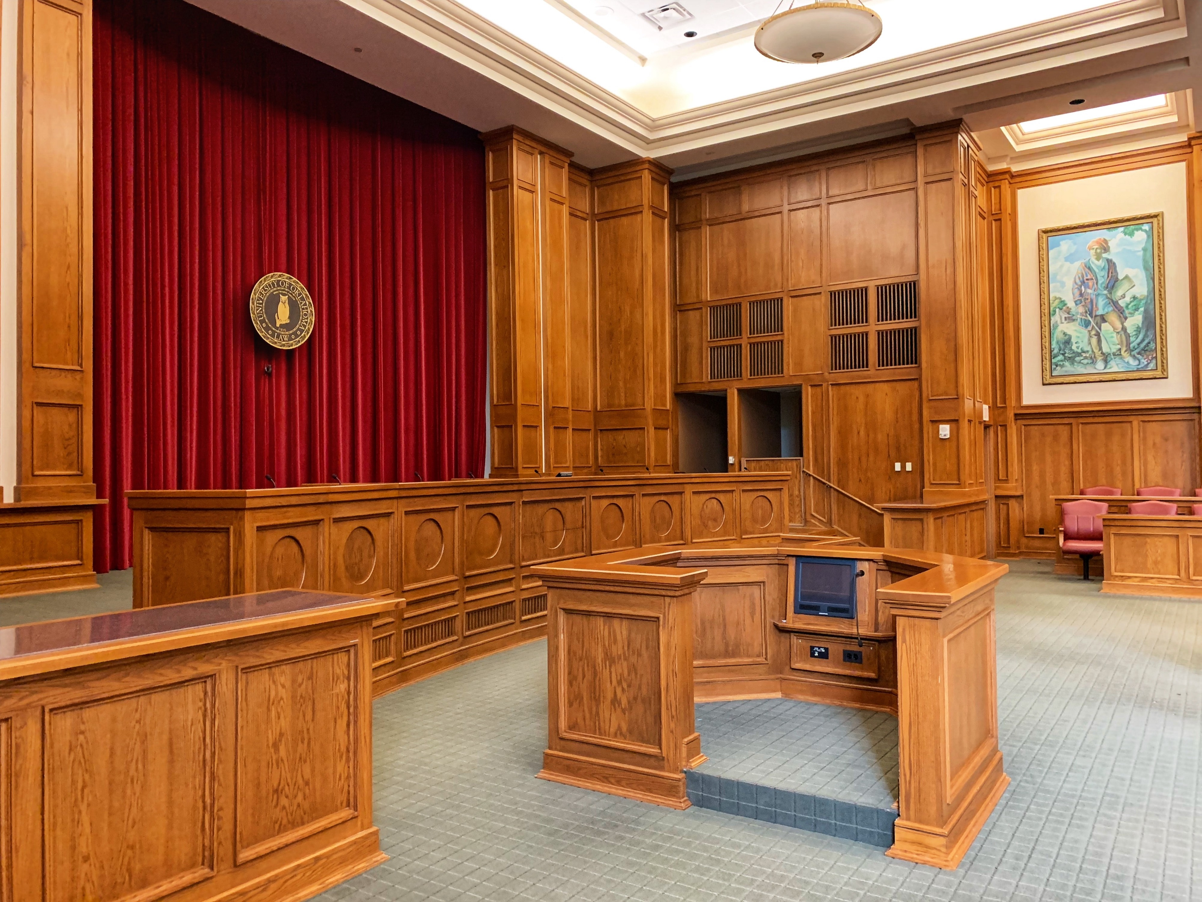 Old-style courtroom with lots of wood and maroon velvet drapes