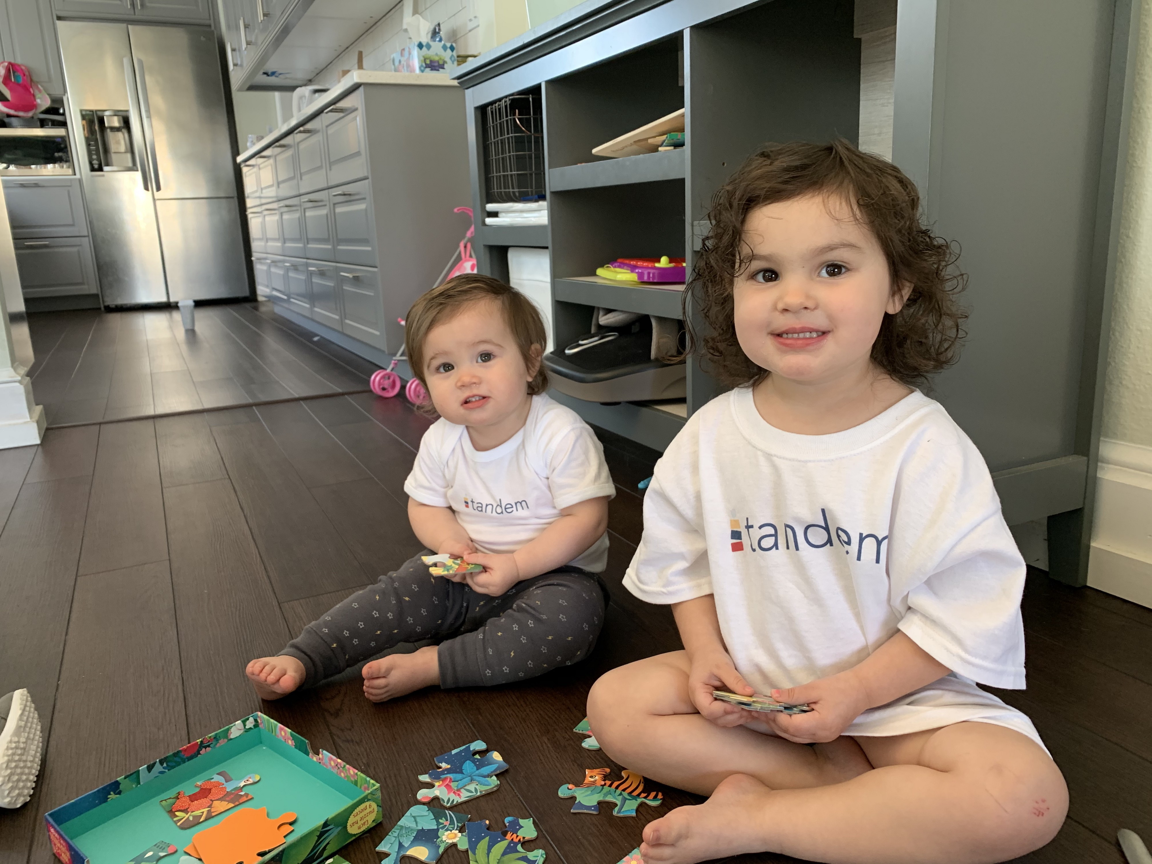 Two toddlers in Tandem tee shirts attempting to put a puzzle together.