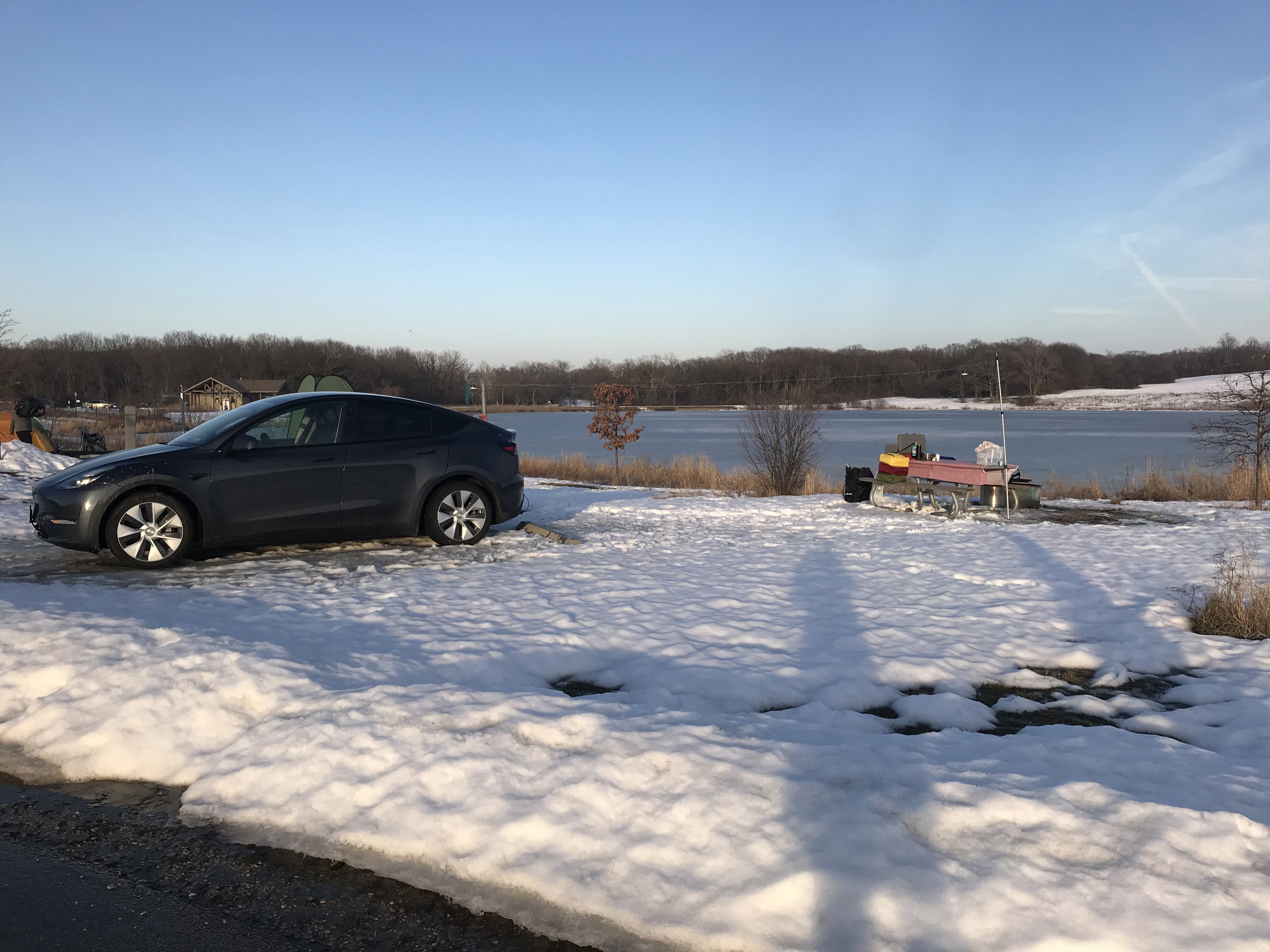 tesla model sits on snow ground in campground near lake