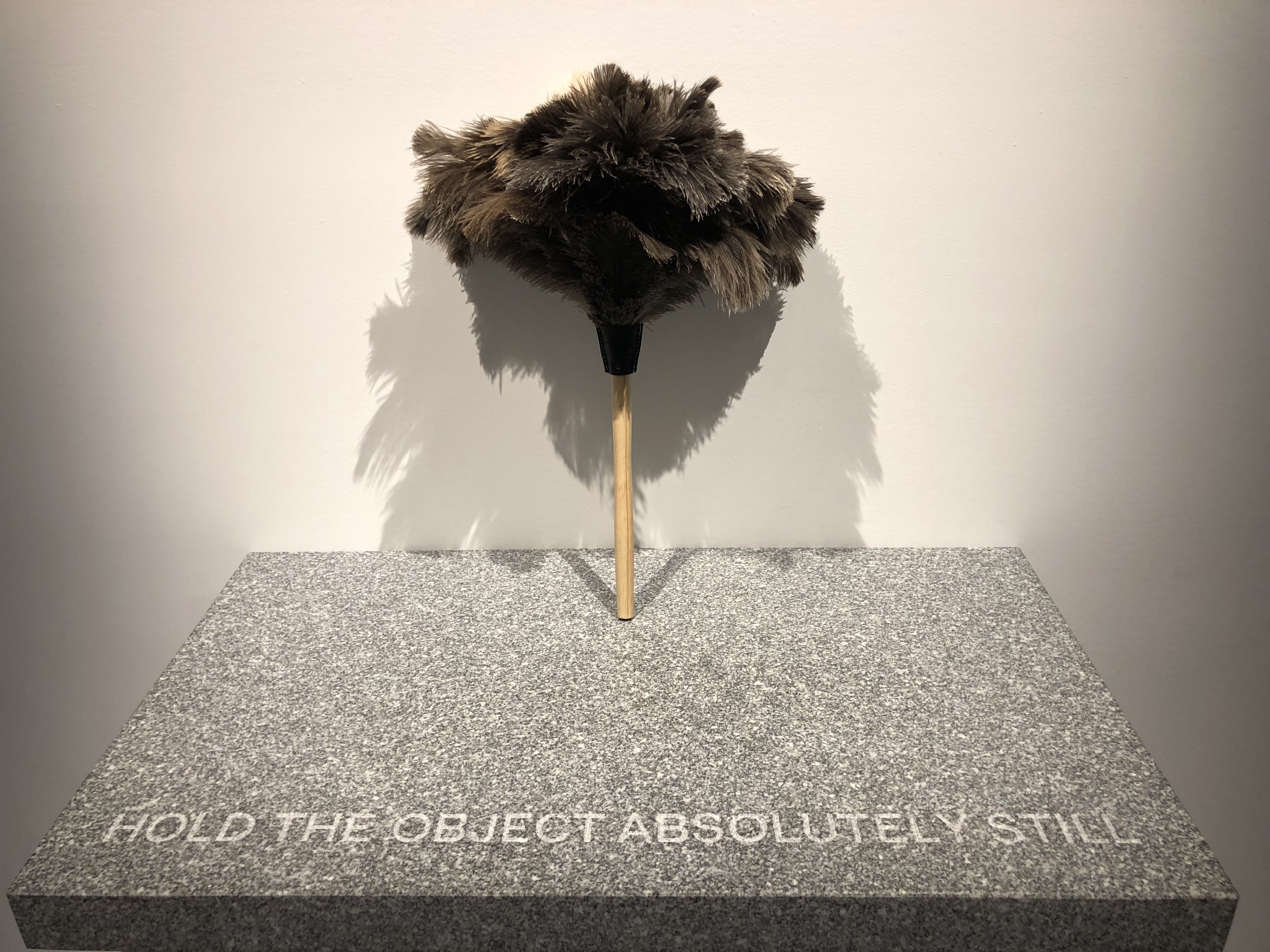 "Feather duster on granite pedestal with ""Hold the object absolutely still"" etched into it"