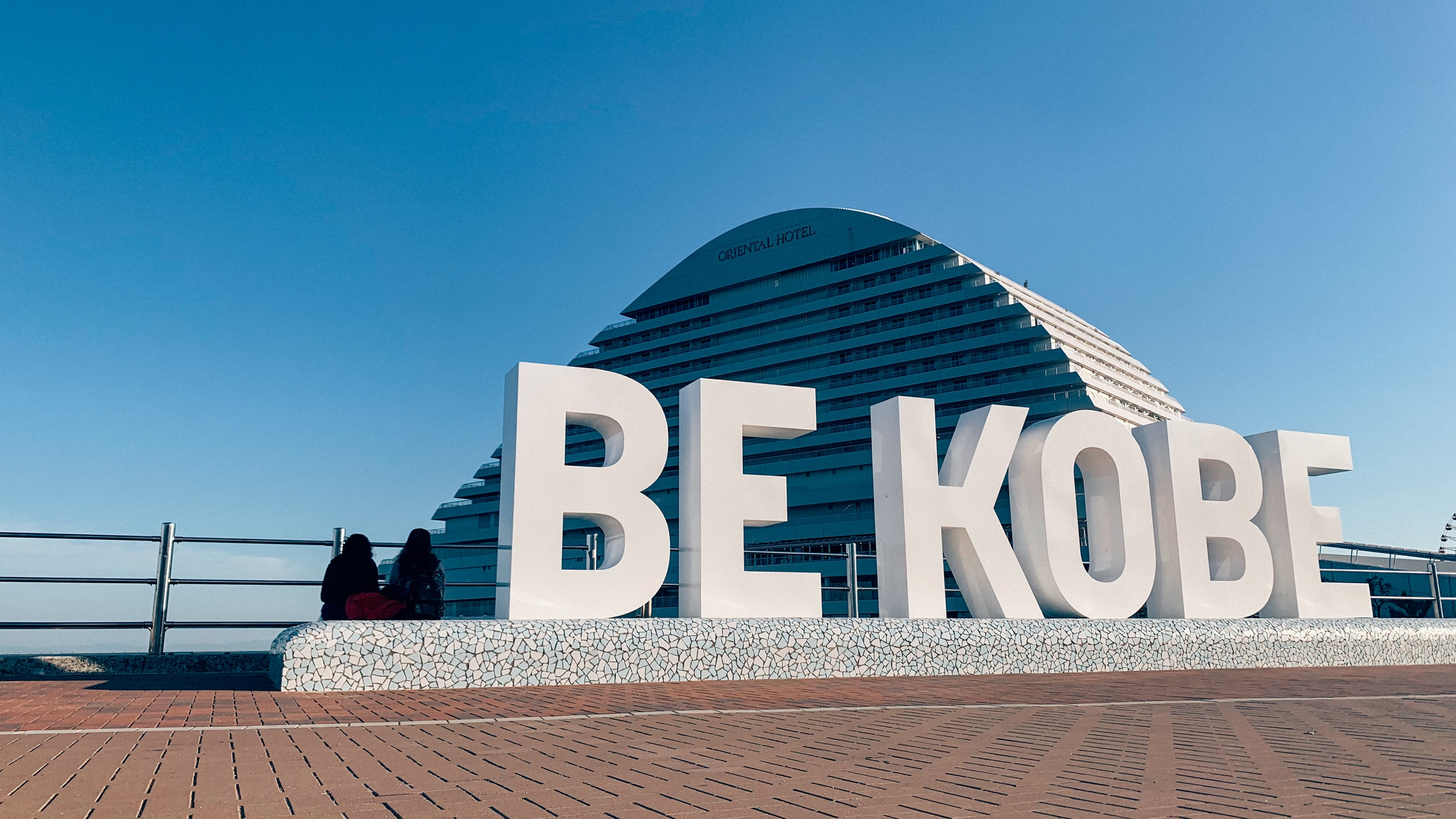 "Large domed building with large white letters in front that say ""Be Kobe"""