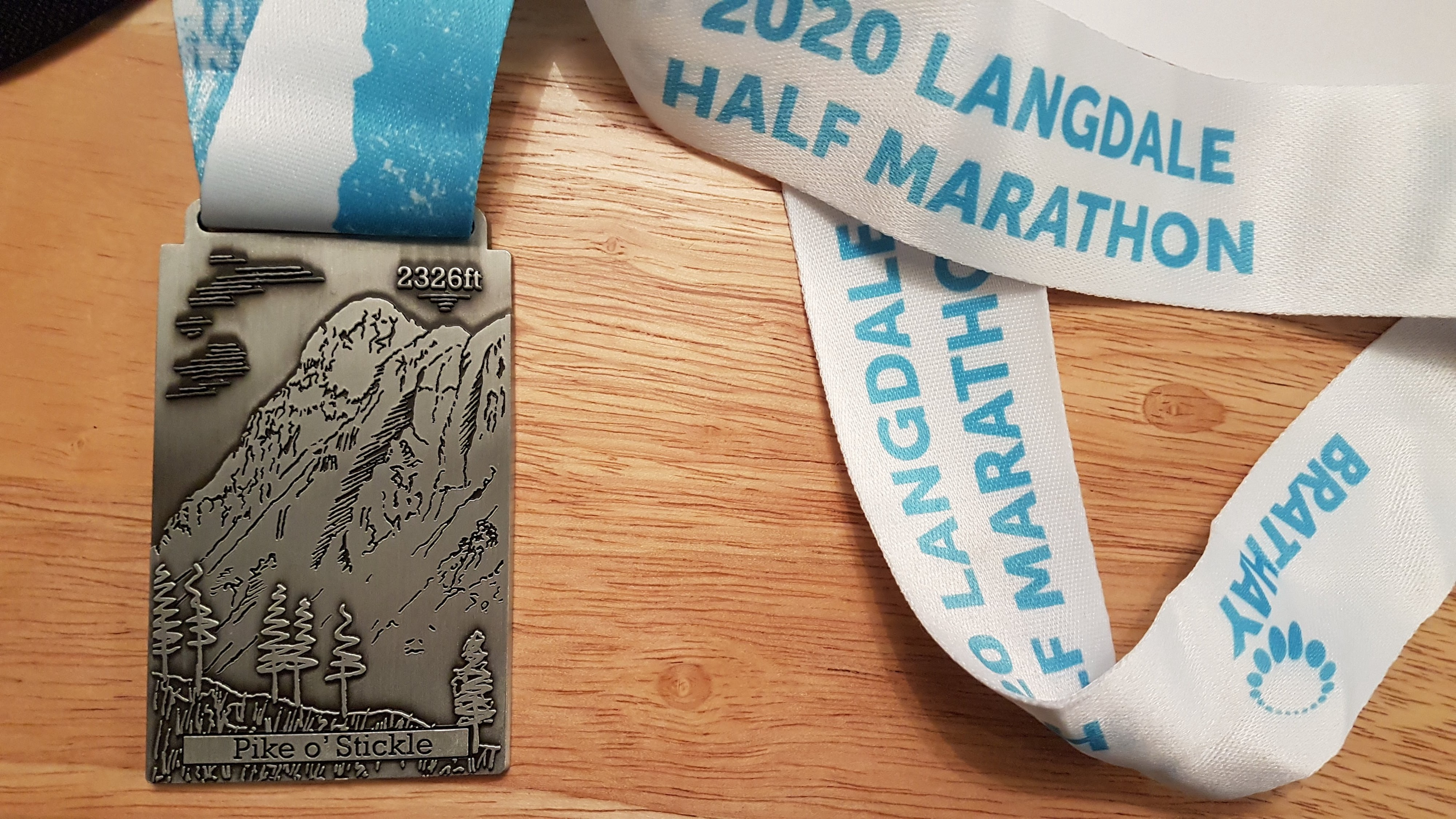 A rectangular medal showing a relief of Pike O'Stickle on a blue and white 2020 Langdale Half Marathon ribbon.